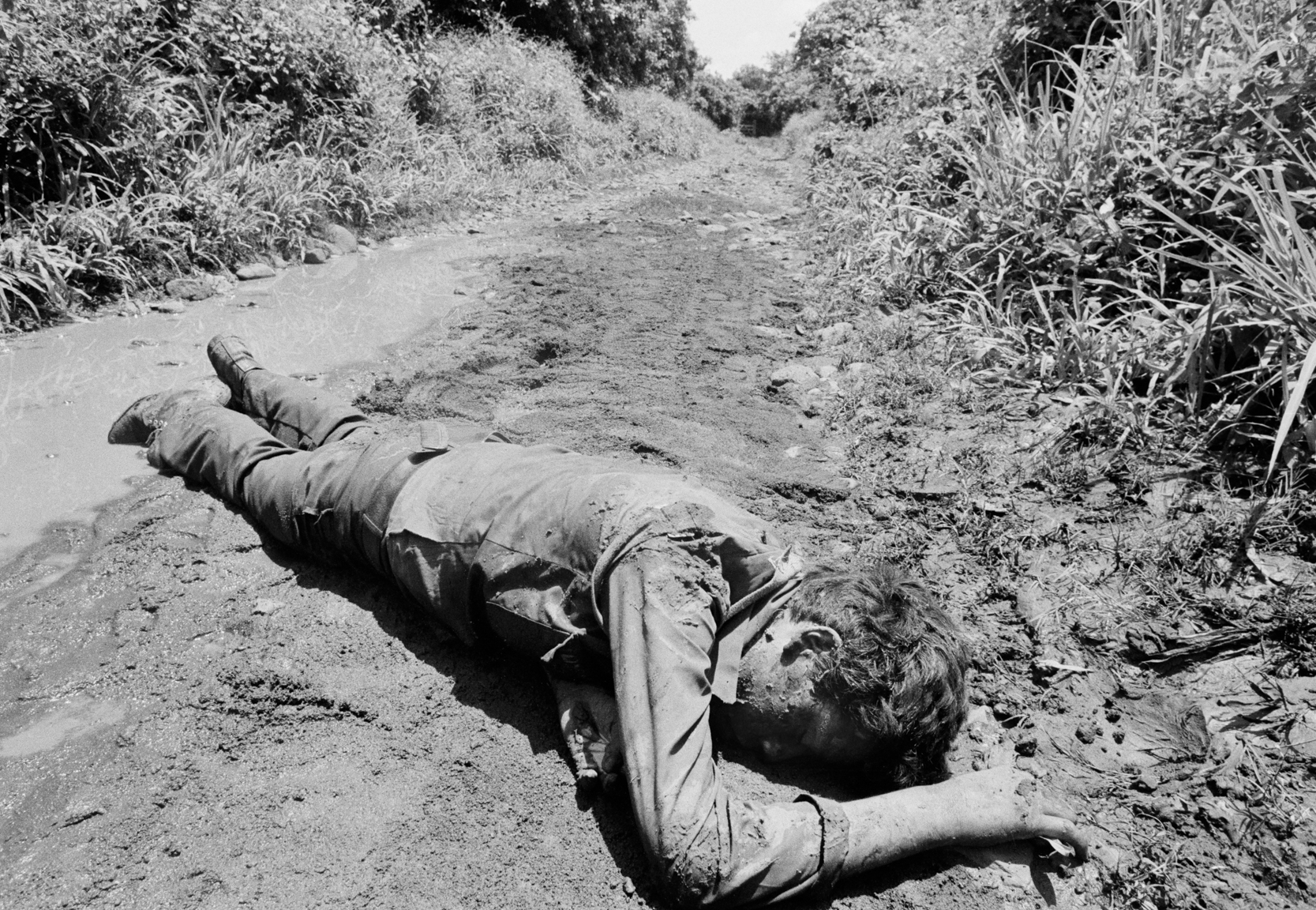View of the corpse of an unidentified People's Revolutionary Army (ERP) guerrilla on a muddy dirt road September 1983 in San Miguel department, El Salvador. At the time, the country was engaged in what became a 13-year civil war between successive right-wing governments and various armed guerrilla factions that eventually claimed over 75,000 lives before ending in 1992.