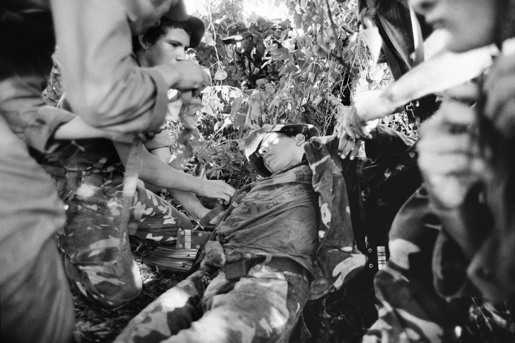 Salvadoran army soldiers of the Atlacatl battalion tend to a wounded soldier during a military operation September 1983 in San Miguel department, El Salvador. The Atlacatl battalion was the first U.S.-trained battalion of the Salvadoran army and here are in pursuit of guerrilla forces belonging to the Ejército Revolucionario del Pueblo, or ERP, one of the five leftist guerrilla organizations that comprised the Frente Farabundo Martí para la Liberación Nacional, FMLN.