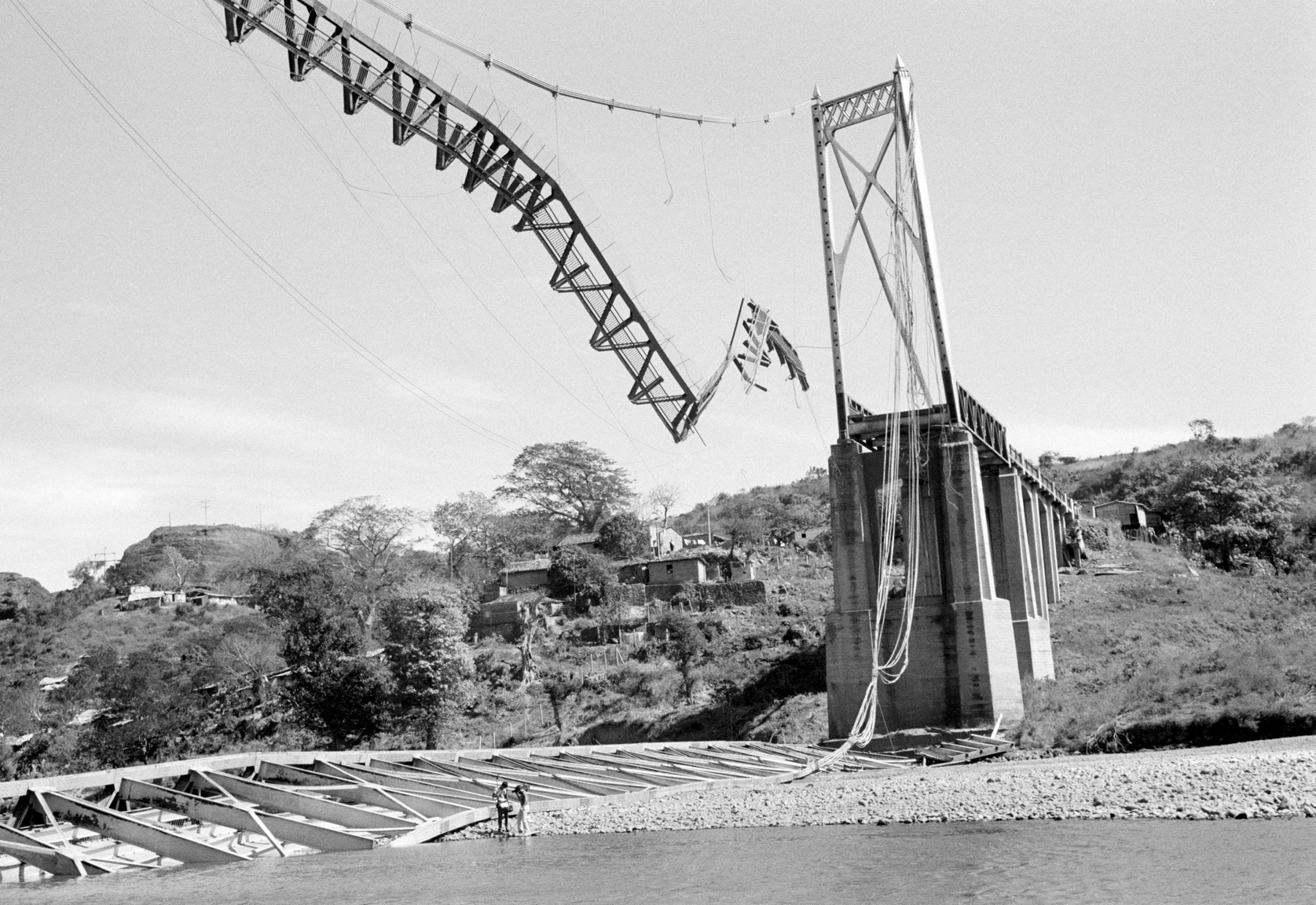 A television news crew inspects the damaged suspension bridge crossing the Lempa River January 3, 1984 that was recently bombed by leftist guerrillas in Cuscátlan, El Salvador. The 800-foot bridge is the largest in El Salvador and the largest in Central America.