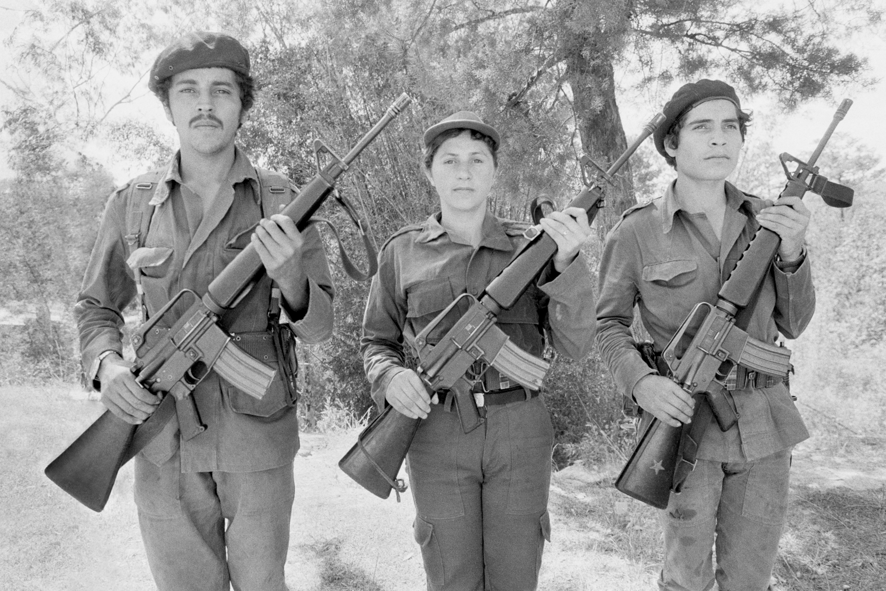 Three leftist guerrillas from the Fuerzas Populares de Liberación, FPL, show off their U.S. made M-16 rifles at a demonstration of force rally February 6, 1983 in La Palma, El Salvador. Weapons used by Salvadoran leftist guerrillas were purchased through black market arms dealers or captured from Salvadoran army soldiers who had received them from the U.S. Pentagon.