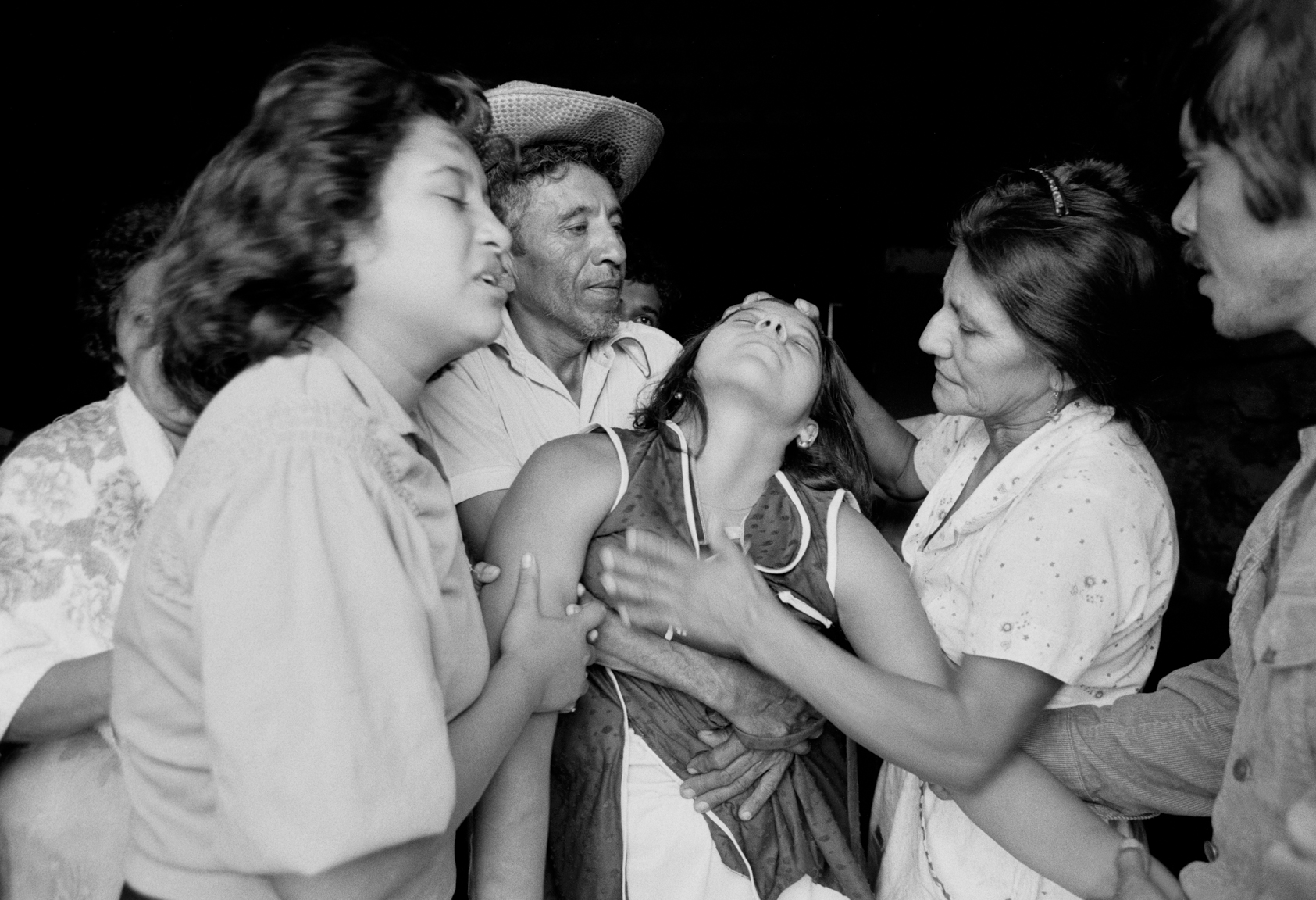 The sister of a civil defenseman, center, faints after hearing about the death of her brother during an overnight attack July 1982 on the brother's military post in Santa Clara, El Salvador. Guerrillas from the FMLN attacked overnight killing 6 civil defensemen before Salvadoran army soldiers arrived the next morning retaking the town, 50 kms from the capital, San Salvador.