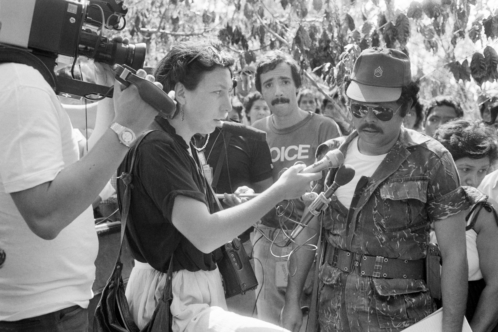 French radio journalist Edith Caron, center, interviews a Salvadoran National Guardsman, right, April 7, 1984, regarding the death of 6 Salvadoran civilians killed by members of a Civil Defense unit and thrown down a nearby well on July 26, 1981 in Los Mangos, Armenia, El Salvador. Eight Civil Defense members were implicated in the killings but no one was convicted.