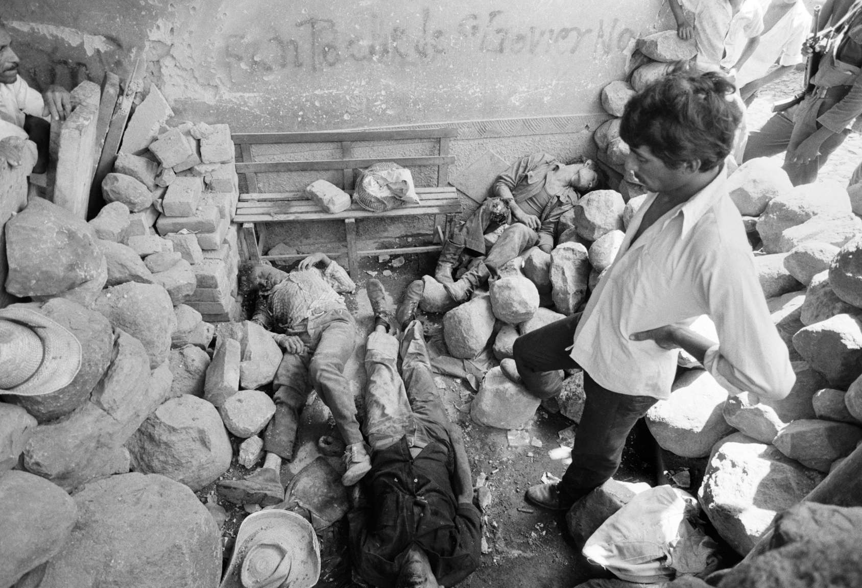 Civilians look over the dead bodies of 3 civil defensemen killed during an overnight attack by FMLN guerrillas July 1982 on a civil defense post in Santa Clara, El Salvador. Guerrillas attacked the town killing 6 civil defensemen before Salvadoran army soldiers arrived the next morning retaking the town, 50 kms from the capital, San Salvador.