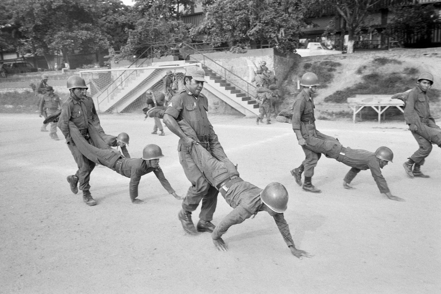 Salvadoran Army recruits practice teamwork drills led by a Salvadoran officer trained at Fort Benning, Georgia in the United States July 1982 at an army base in San Miguel, El Salvador. At the time, the country was engaged in what became a 13-year Civil War between successive right-wing governments (backed by the US and others) and various armed guerrilla factions that eventually claimed over 75,000 lives before ending in 1992.