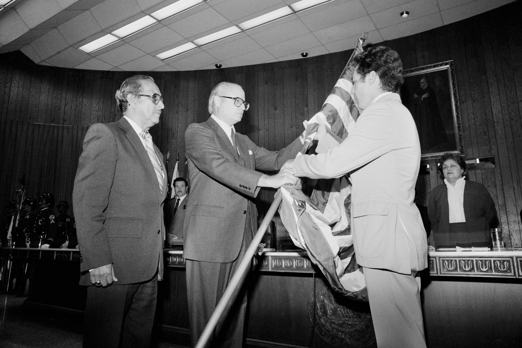 U.S. Ambassador Deane Hinton, center, hands an American flag to President of the Constituent Assembly Roberto D'Aubuisson April 1984. At the time, D'Aubuisson was the first leader of the Nationalist Republican Alliance (ARENA) and had been named as the primary suspect who ordered the assassination of Archbishop Óscar Romero in 1980.