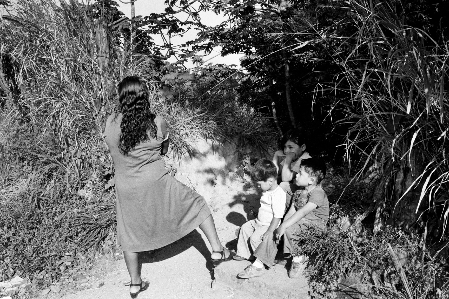 A woman and her children wait for bus transportation March 1983 in the Mejicanos neighborhood of San Salvador, El Salvador.