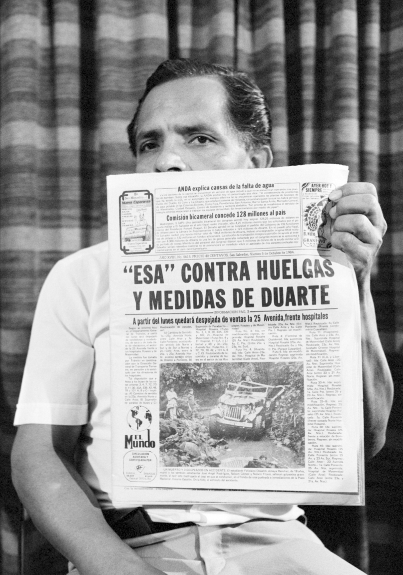 A leader of a left-wing labor union, MUSYGES, displays a headline in El Mundo daily newspaper reporting threats to them at a press conference from the death squad, the Secret Anticommunist Army, ESA, that is against strikes and measures by El Salvador's President Napolean Duarte to allow strikes October 5, 1984 in San Salvador, El Salvador.