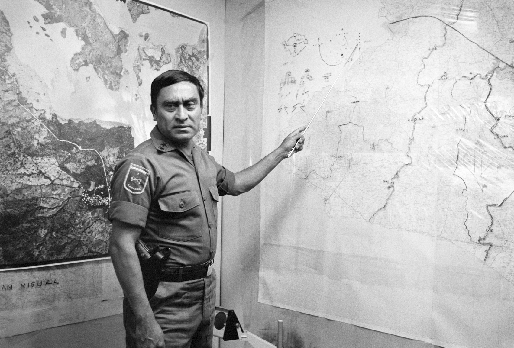 Col. Sigfredo Ochoa Pérez, commanding officer of the U.S.-trained Cabañas Battalion, points to a map describing leftist FMLN guerrilla movement and infiltration routes October 1983 at his military headquarters in Sesuntepeque, El Salvador. Col. Ochoa was commander of Destacamiento Militar 2 and known as an aggressive counterinsurgency officer unafraid to use killing zone tactics and to kill civilians he suspected of being leftist guerrilla supporters.