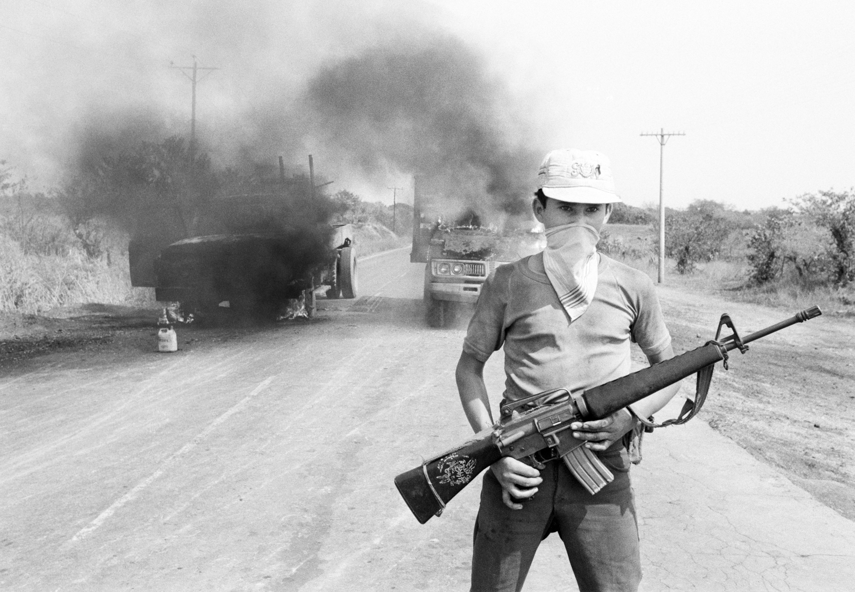 A member of the Salvadoran guerrilla group Ejército Revolucionario del Pueblo, or ERP, stands in front of two burning commercial vehicles on the Pan American Highway March 1, 1983 in Usulatan, El Salvador. Controlling areas of eastern El Salvador, the ERP would target and burn vehicles traveling on the highway if a commercial strike had been called to show defiance of Salvadoran government control.