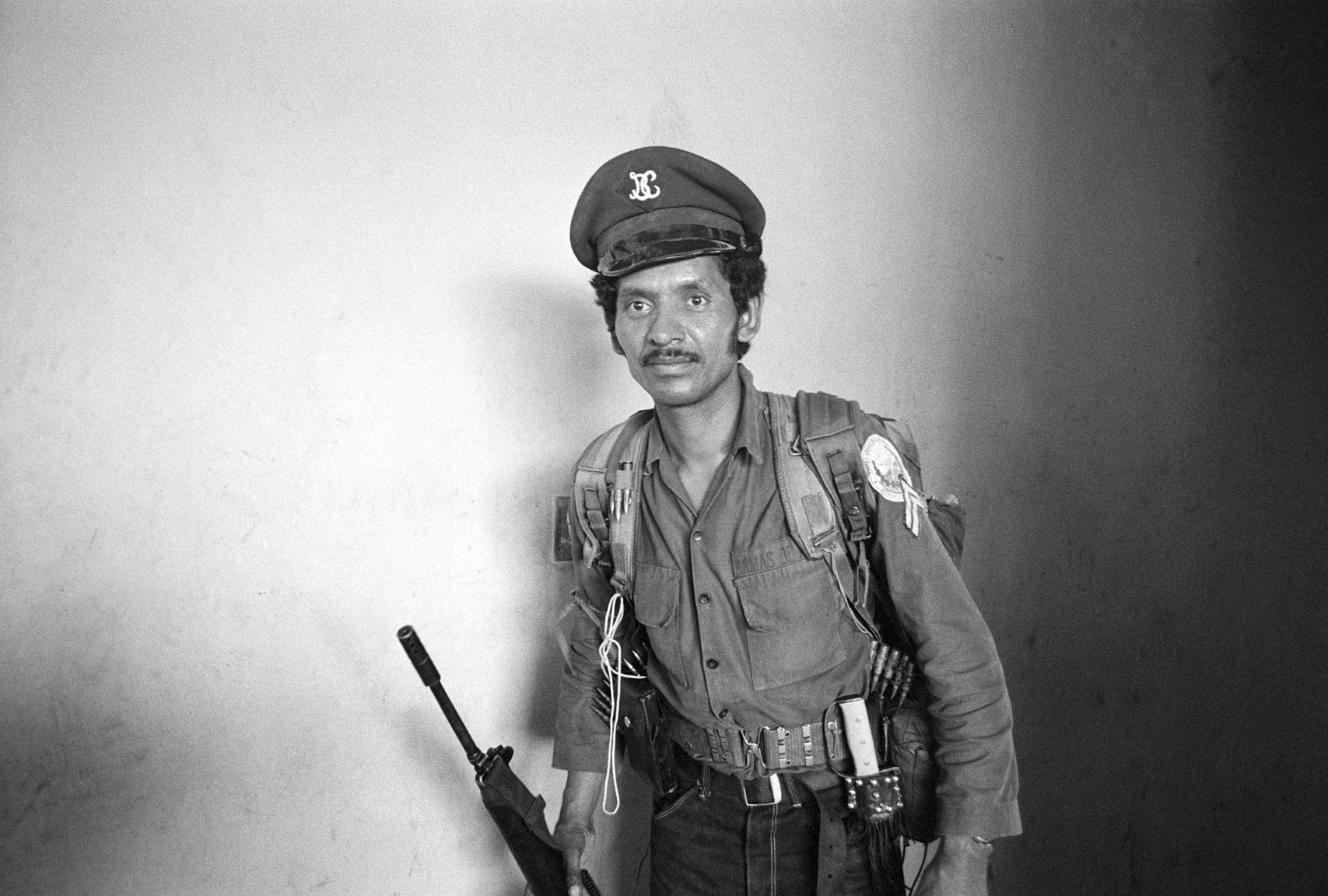 A member of the Salvadoran guerrilla group Ejército Revolucionario del Pueblo, or ERP, moves through the ransacked office of the national telephone company February 1, 1983 in Jucuapa, El Salvador. The guerrilla's uniform is a mix of captured clothing of the Salvadoran government's security forces.