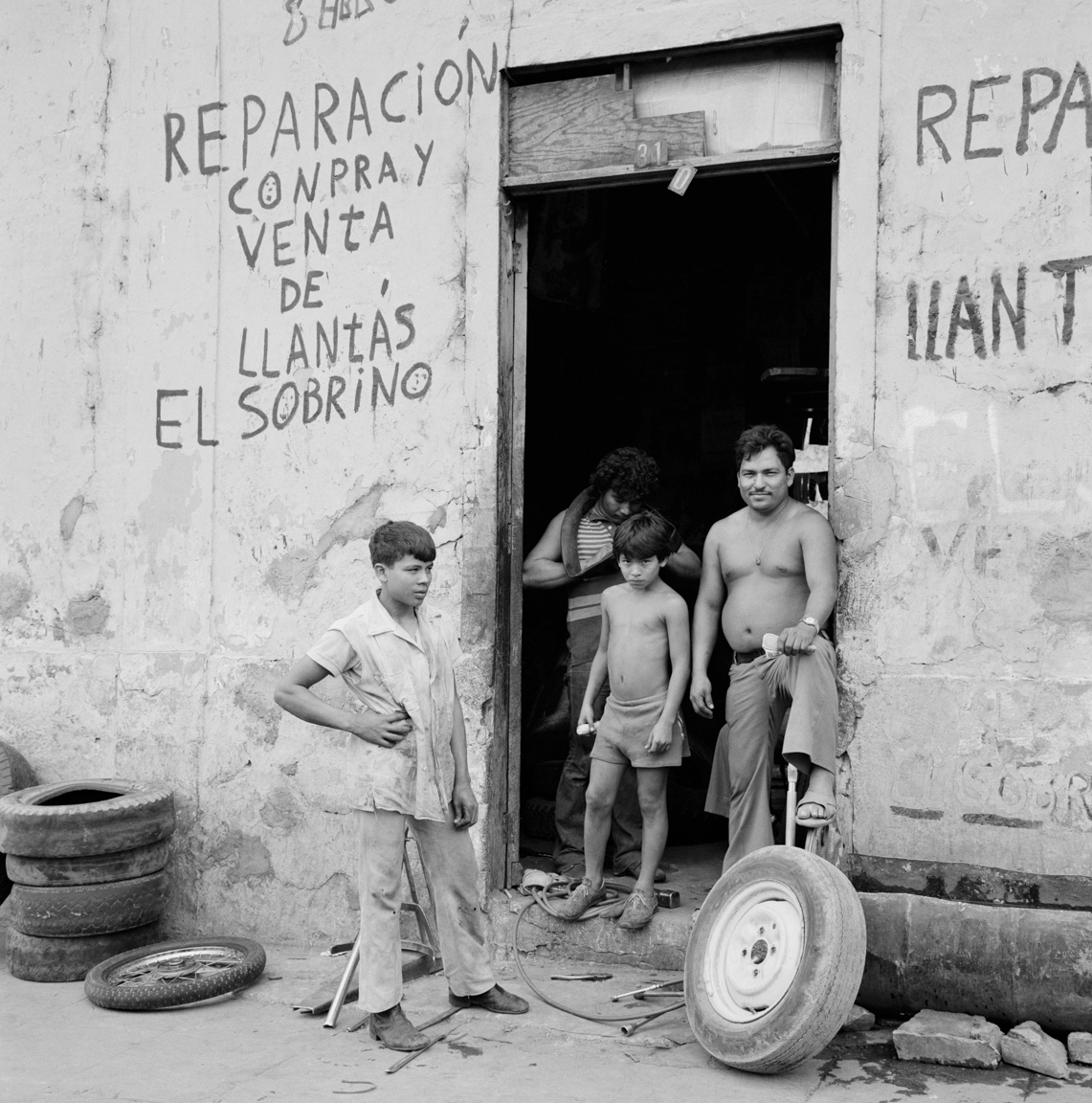 The owner of a tire repair shop and his children work on flat tires on a side street January, 1984 in downtown San Salvador.