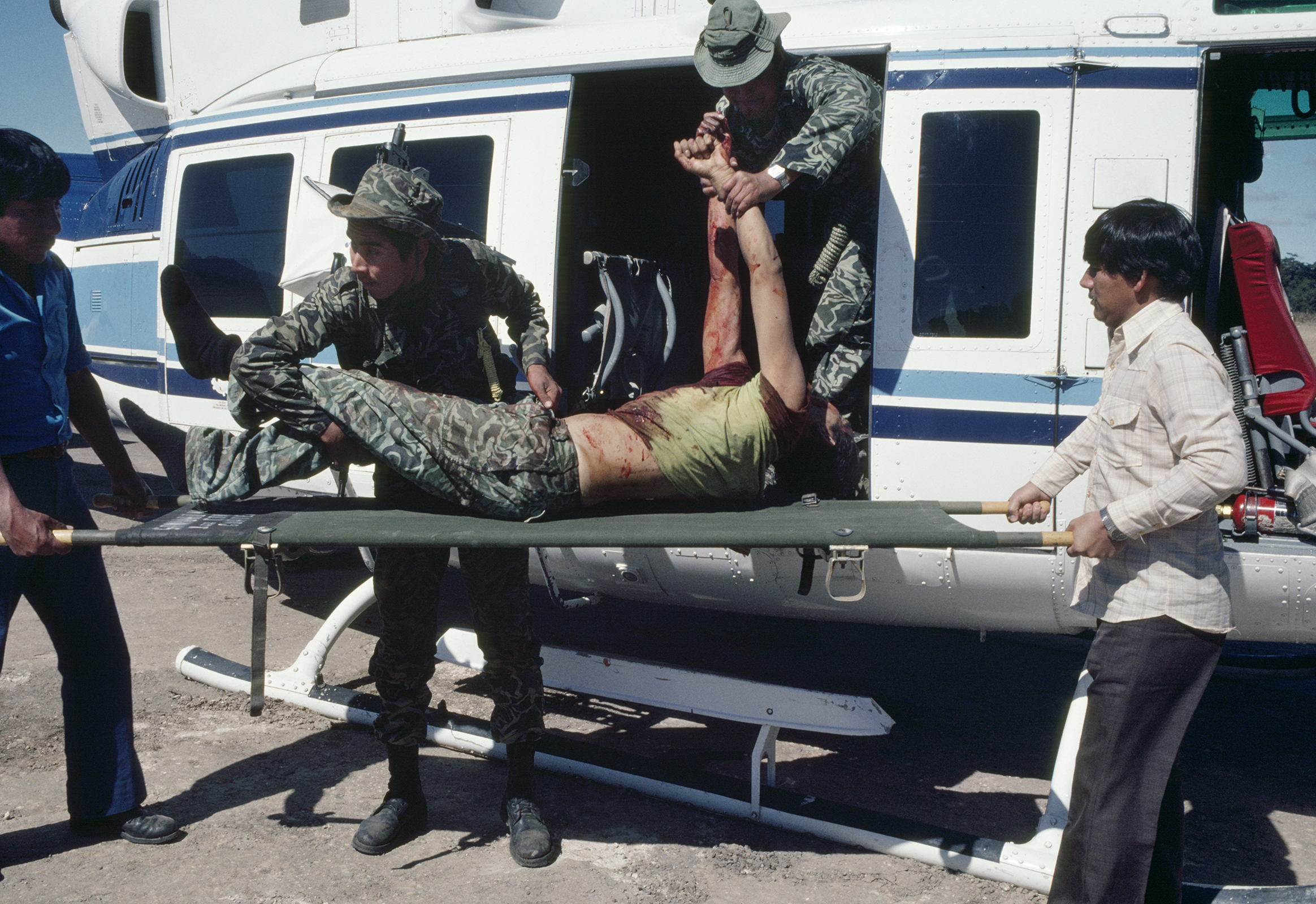 Guatemalan army soldiers transfer a dead soldier from a helicopter to a stretcher in Santa Cruz del Quiché, Guatemala, January 20, 1982. On January 19, 1982, the Guerrilla Army of the Poor, EGP, attacked the army garrison in San Juan Cotzal, 60 miles north, with a reported 300 insurgents killing 37 government soldiers.