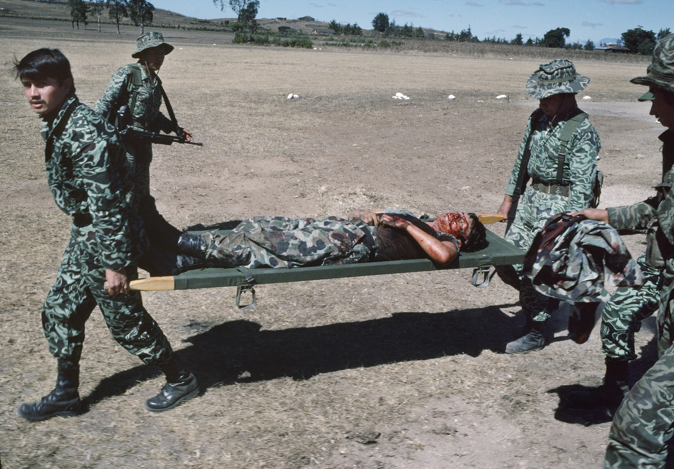 Guatemalan army soldiers carry a dead soldier brought to the army hospital in Santa Cruz del Quiché, Guatemala, January 20, 1982. On January 19, 1982, the Guerrilla Army of the Poor, EGP, attacked the army garrison in San Juan Cotzal, 60 miles north, with a reported 300 insurgents killing 37 government soldiers.