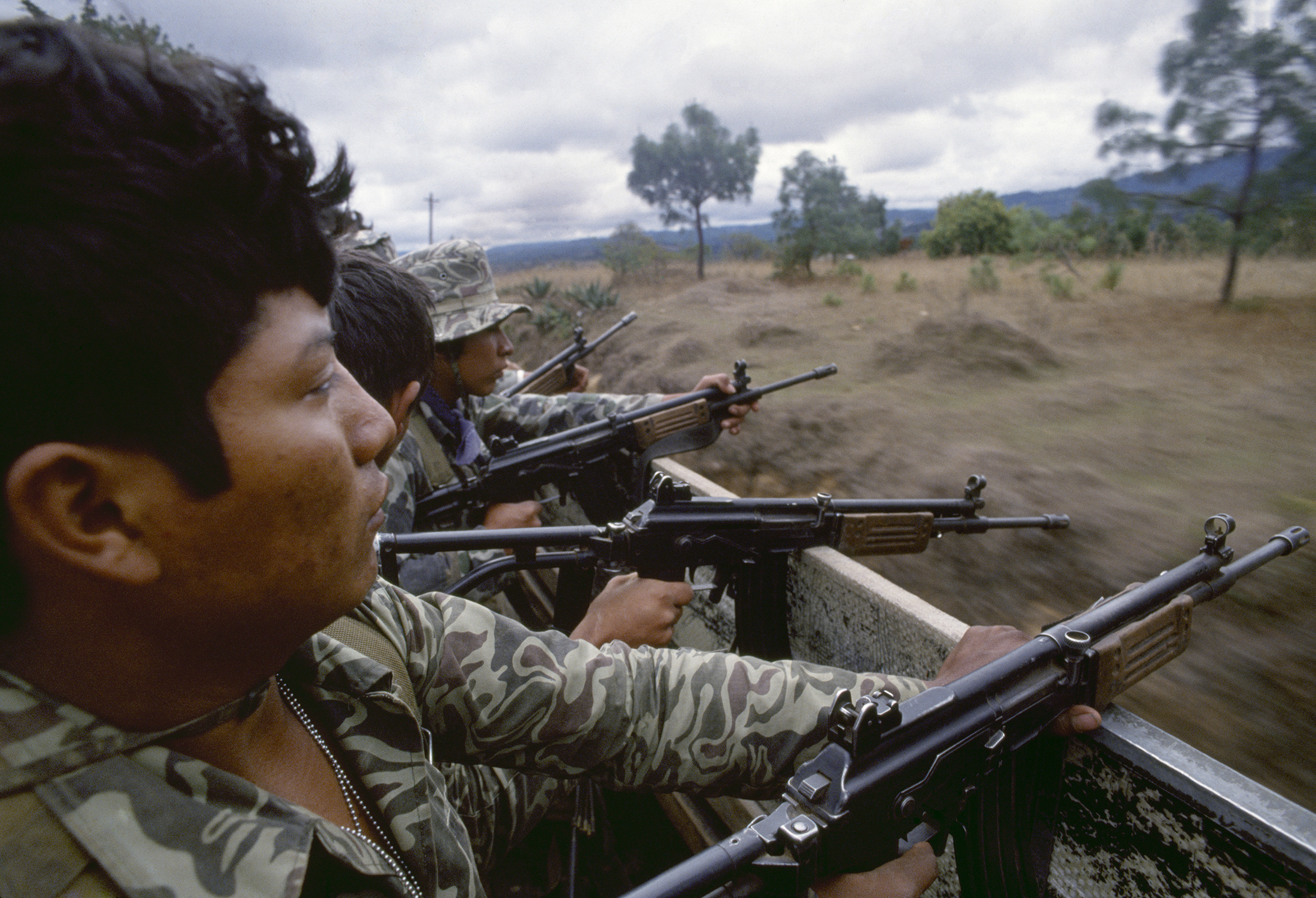 Guatemalan army soldiers armed with Israeli-supplied Galil assault rifles travel in a U.S. manufactured troop transport through possible guerrilla ambush terrain outside of Santa Cruz del Quiché on February 1, 1982. Despite its abysmal human rights record, the Guatemalan state received irregular military aid and support from the United States, along with Israel and Argentina, throughout the armed conflict to fund its oppressive counterinsurgency campaigns.