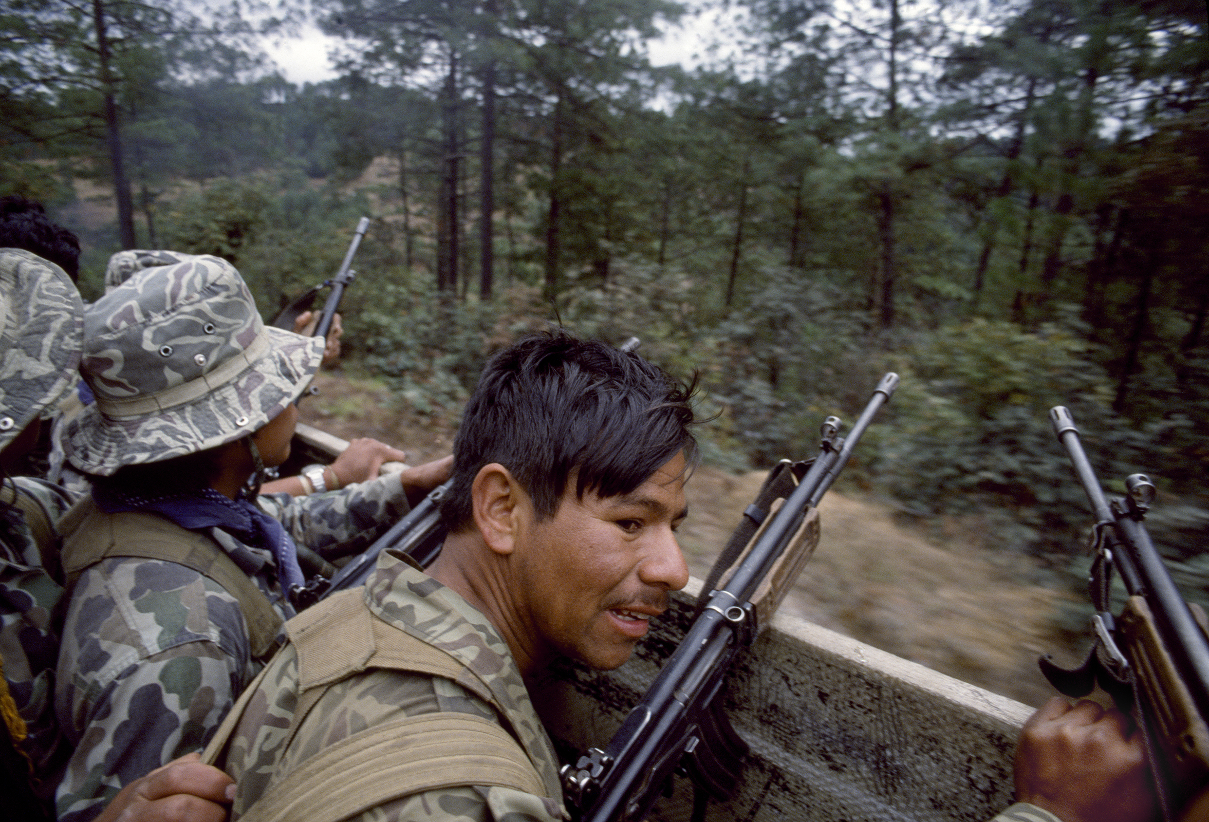 Guatemalan army soldiers armed with Israeli-supplied Galil assault rifles travel in a U.S. manufactured troop transport through possible guerrilla ambush terrain outside of Santa Cruz del Quiché on February 1, 1982.
