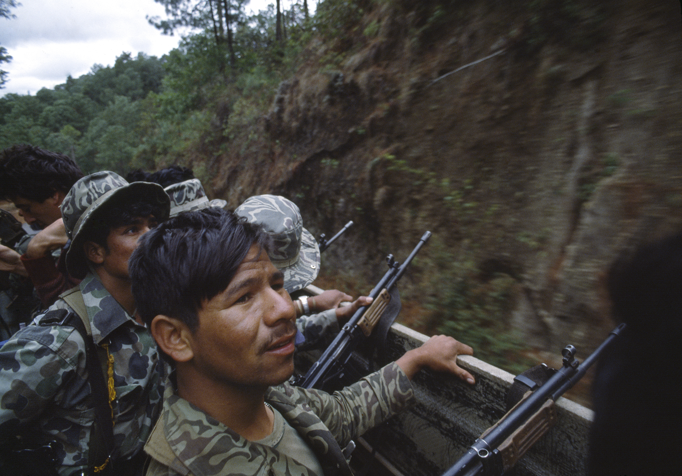 Guatemalan army soldiers armed with Israeli-supplied Galil assault rifles travel in a U.S. manufactured troop transport through possible guerrilla ambush terrain outside of Santa Cruz del Quiché on February 1, 1982. Many army officers had counterinsurgency training given by U.S. Army instructors at the School of the Americas in both the Panama Canal Zone and later in Fort Benning, Georgia.