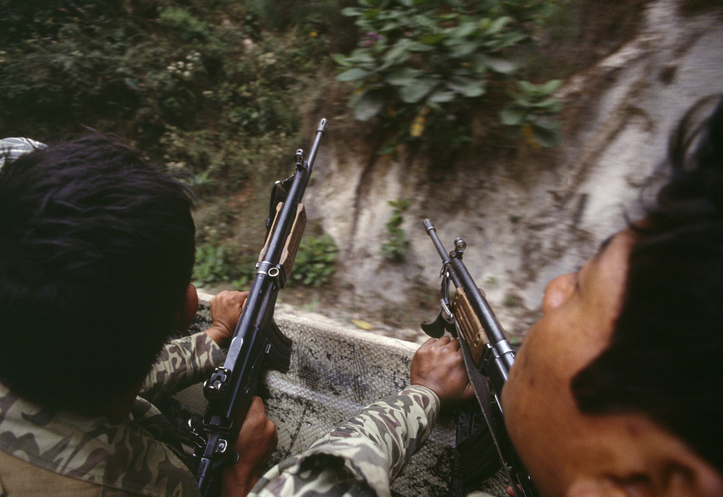 Guatemalan army soldiers armed with Israeli-supplied Galil assault rifles travel in a U.S. manufactured troop transport through possible guerrilla ambush terrain outside of Santa Cruz del Quiché on February 1, 1982. Guerrilla ambushes were often in rural mountainous areas.