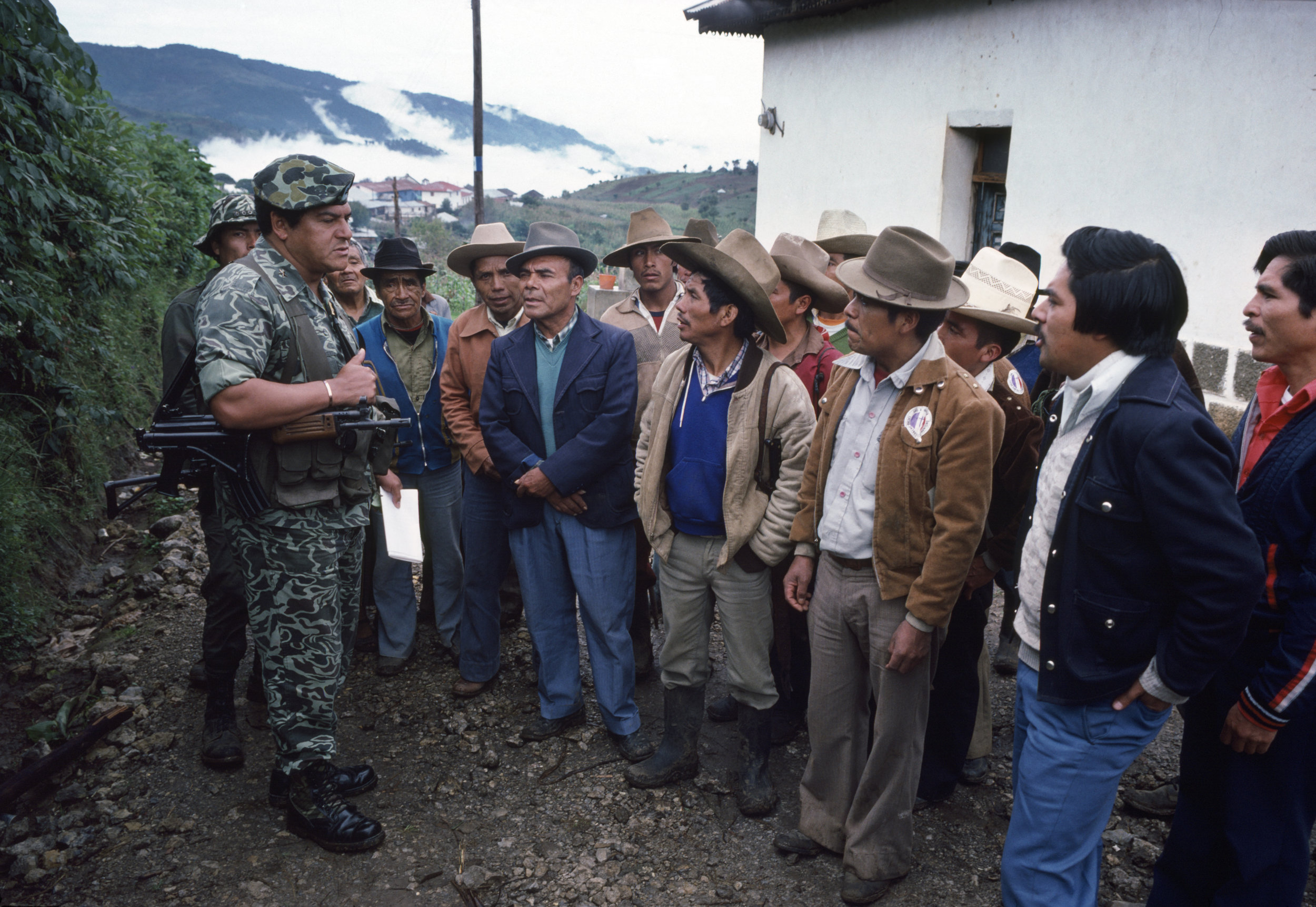 Local male residents listen to a Guatemalan army officer, left, speak about forming Civil Defense Patrols to secure their villages against leftist guerrilla attacks near Huehuetenango, Guatemala on October 1, 1982. The Patrols effectively institutionalized military power at the local level by infiltrating and dissolving community loyalties and reorienting them to serve counterinsurgency efforts. They served a critical role in the systemic violence, inequality, and militarization of the domestic armed conflict.