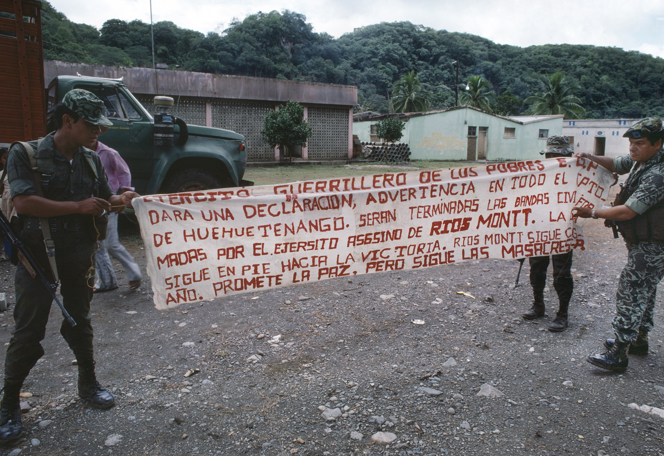 Local residents watch as Guatemalan army soldiers show captured banners made by the militant guerrilla group Guerrilla Army of the Poor, EGP, in Huehuetenango, Guatemala, October 1, 1982.