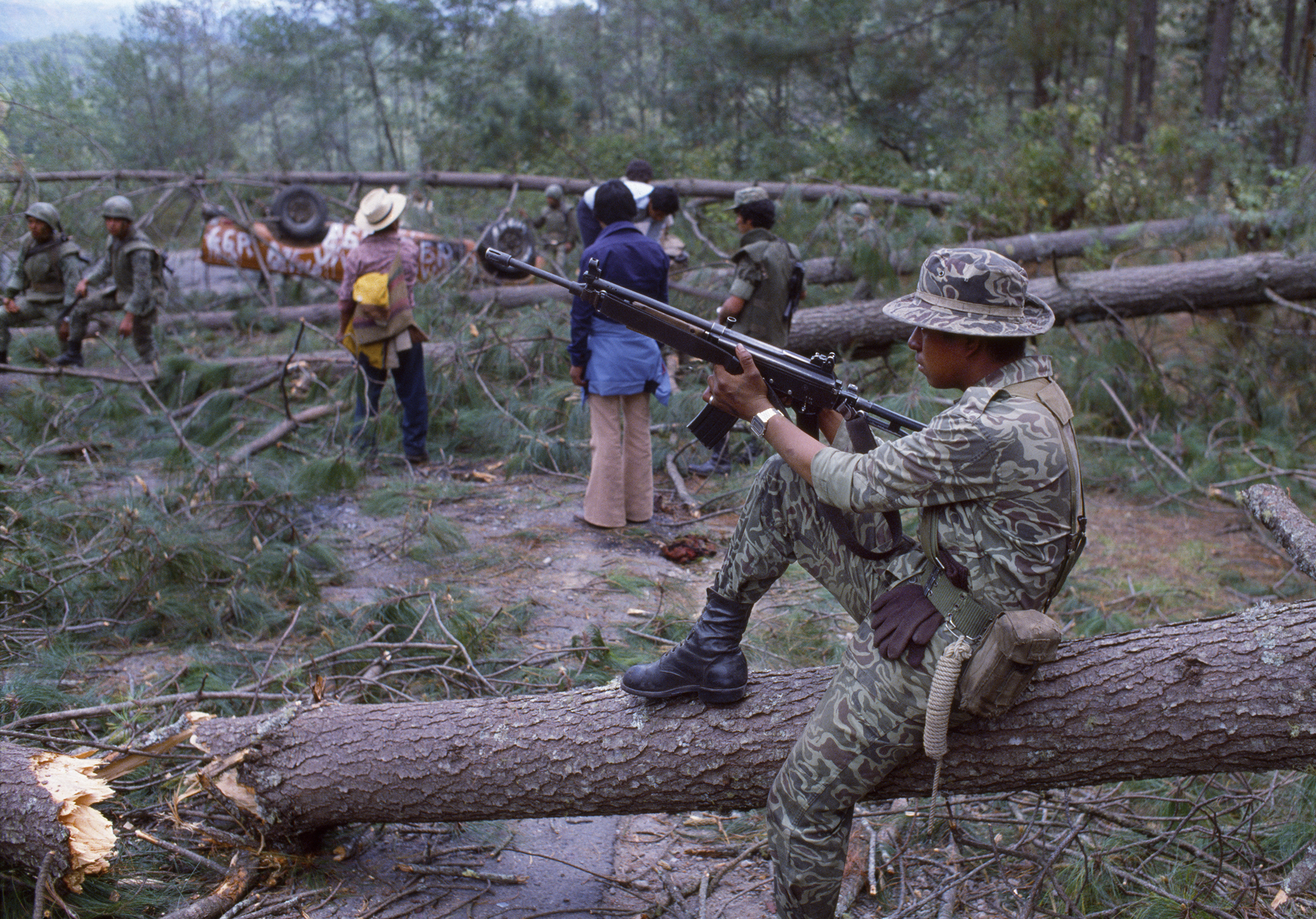 Guatemalan army soldiers, armed with Israeli-supplied Galil assault rifles, and unidentified locals clear a section of the Pan American Highway blocked by felled trees during the ongoing civil war in Los Encuentros, Guatemala March 7, 1982. The trees were cut by the Guerrilla Army of the Poor, EGP, blocking the road the day of presidential elections.