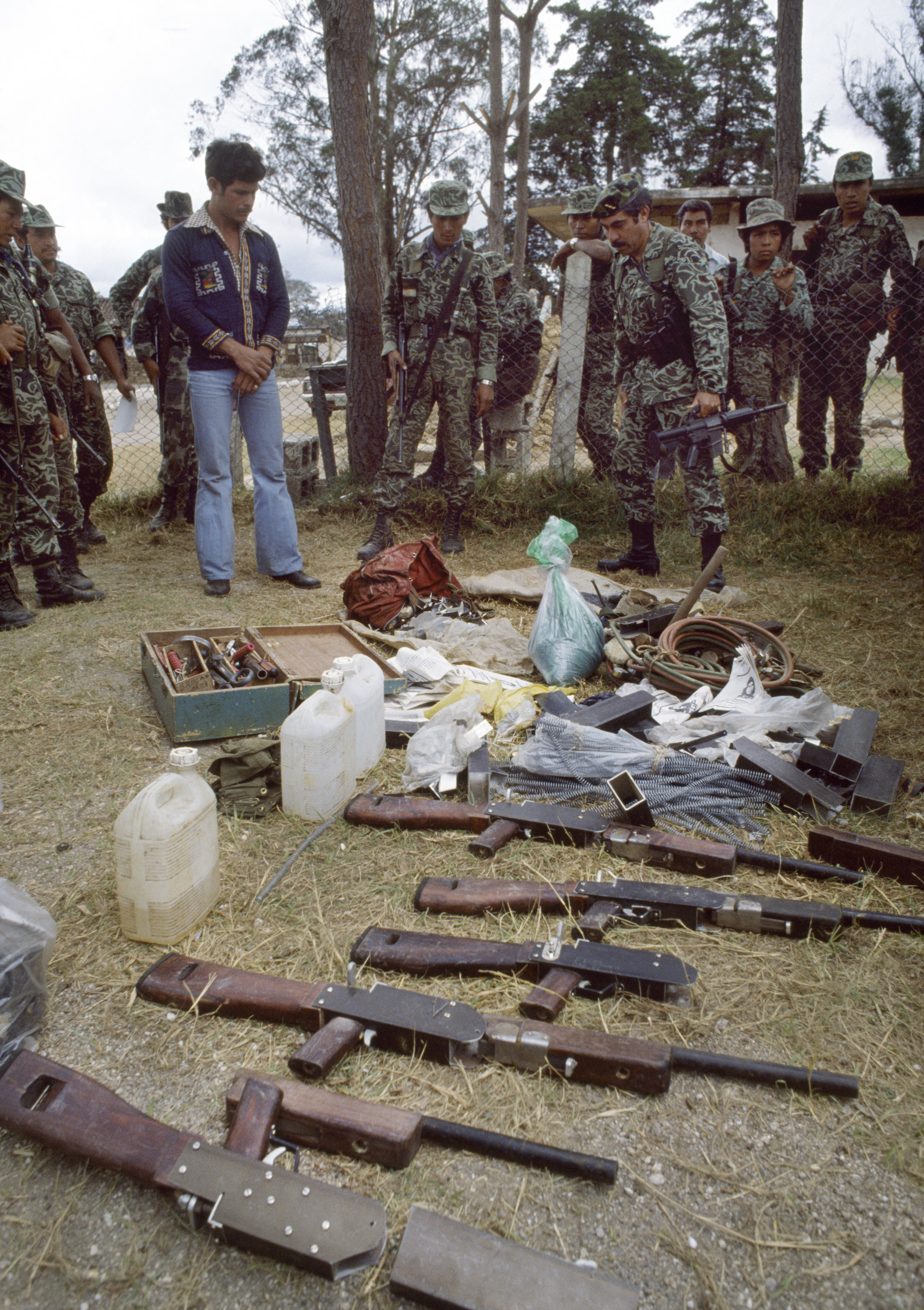 Guatemalan army Colonel Lima Estrada looks over captured weapons and explosives found in a Guerrilla Army of the Poor, EGP, safe house outside of Santa Cruz del Quiché, Guatemala, February 1, 1982. Col. Lima Estrada was the commander of the El Quiché department army garrison.