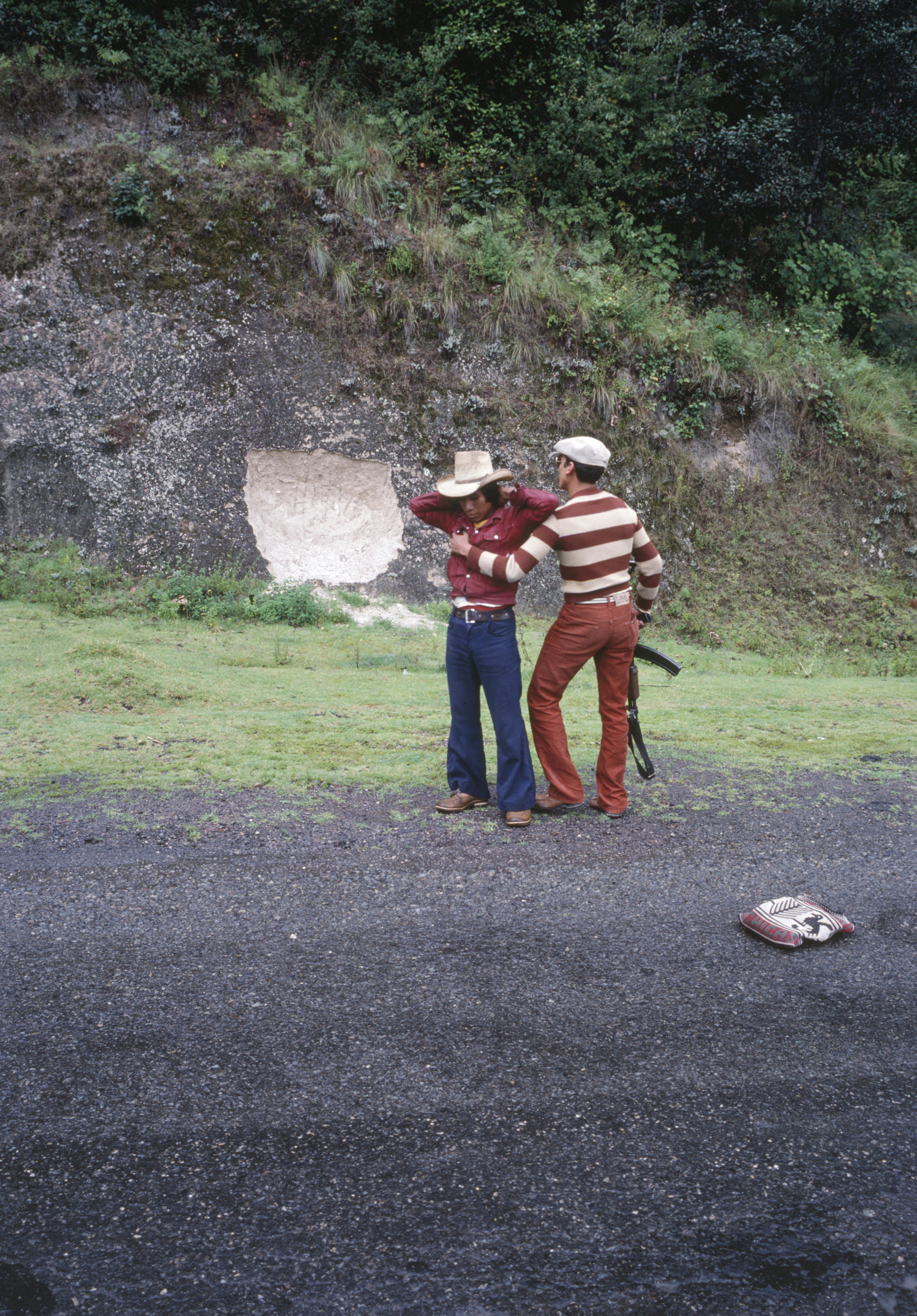 A plainclothes security officer, right, searches a civilian in rural Huehuetenango, Guatemala, September 1, 1982. Civil Defense Patrols effectively institutionalized military power at the local level by infiltrating and dissolving community loyalties and reorienting them to serve counterinsurgency efforts. They served a critical role in the systemic violence, inequality, and militarization of the domestic armed conflict.