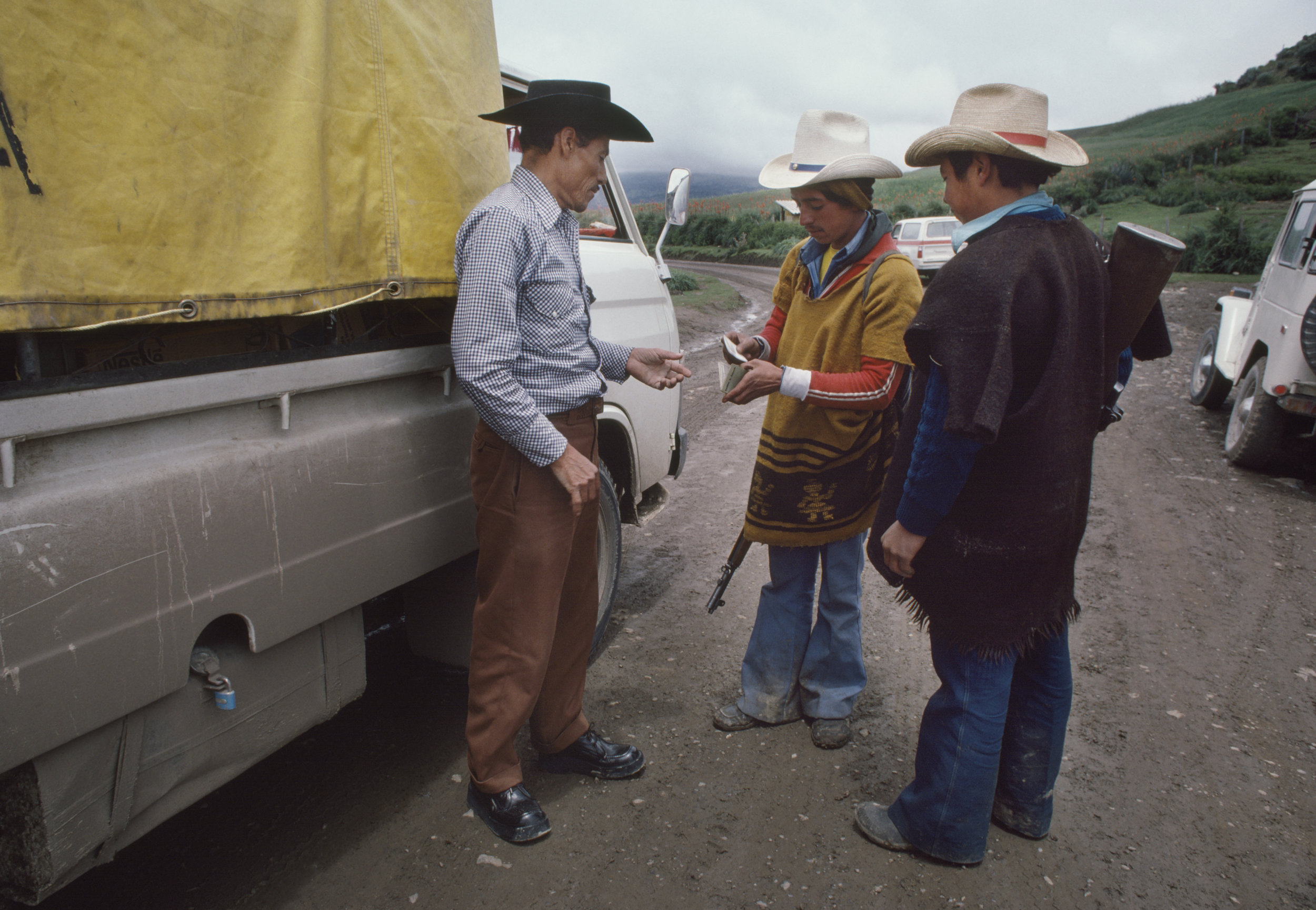 Members of a local Civil Defense Patrol check a truck driver's identity papers along a mountain road in rural Huehuetenango, Guatemala, September 1, 1982.