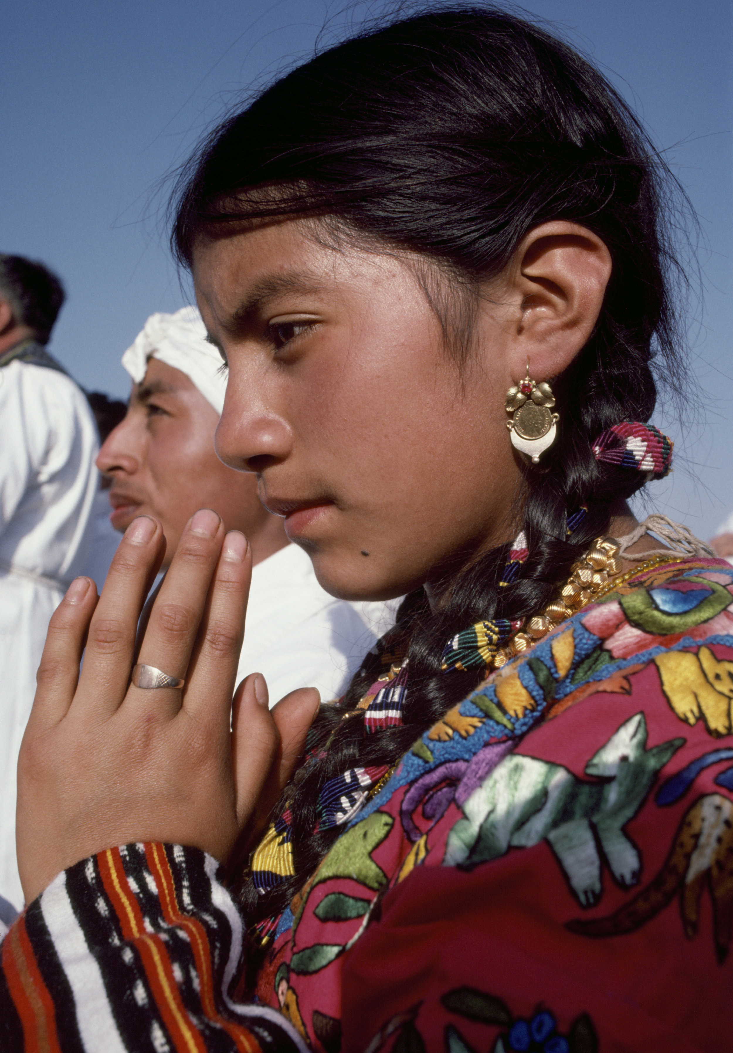A young Maya woman prays during the visit of Pope John Paul ll in Guatemala City, Guatemala, March 7, 1983. During his visit, the Pope condemned the country's human rights atrocities and the state's violence and oppression against its indigenous Maya population.