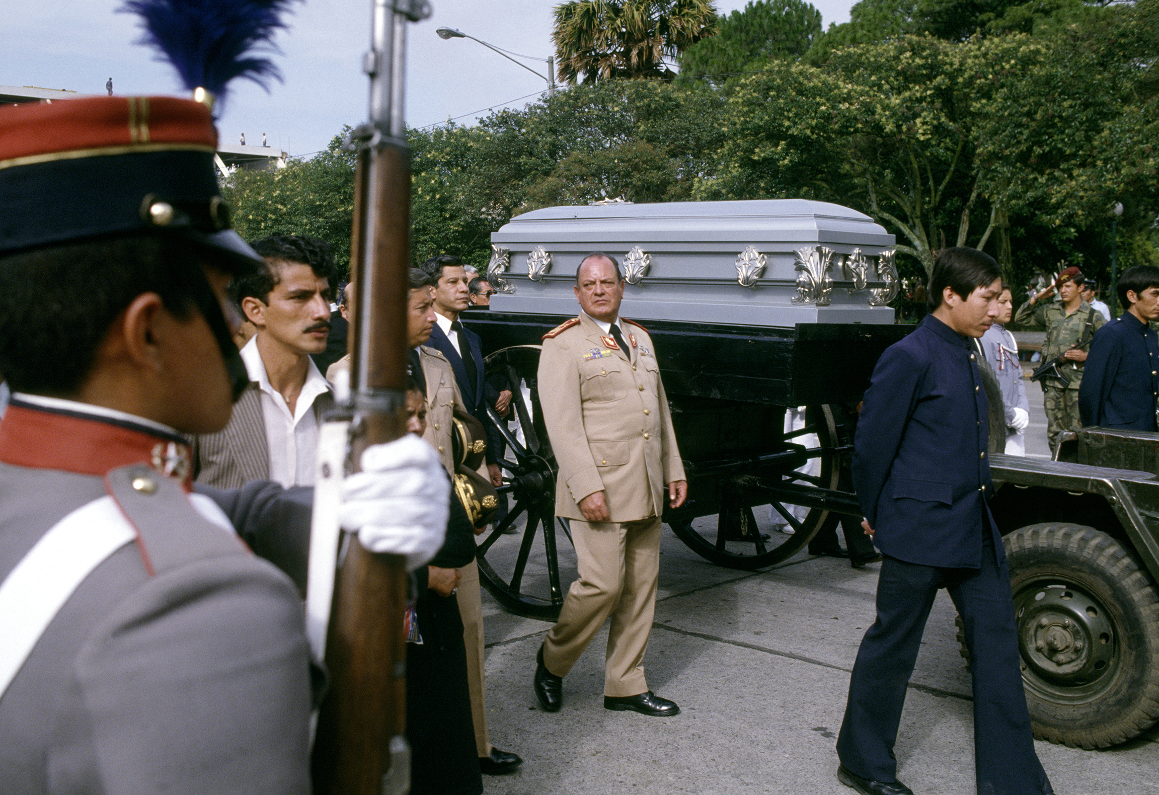Guatemalan Defense Minister Brigadier General Óscar Mejía Víctores, 1930-2016, center, walks along the casket of Cardinal Casariego, Archbishop of Guatemala, who died June 15, 1983 from a heart attack following the March 1983 visit of Pope John Paul ll to Guatemala. General Mejía Víctores deposed President and General Ríos Montt in a coup d'état on August 8, 1983. Mejía has since been indicted in both Spain and Guatemala on charges of genocide, as well as torture and crimes against humanity, for his rule as president in the internal armed conflict.