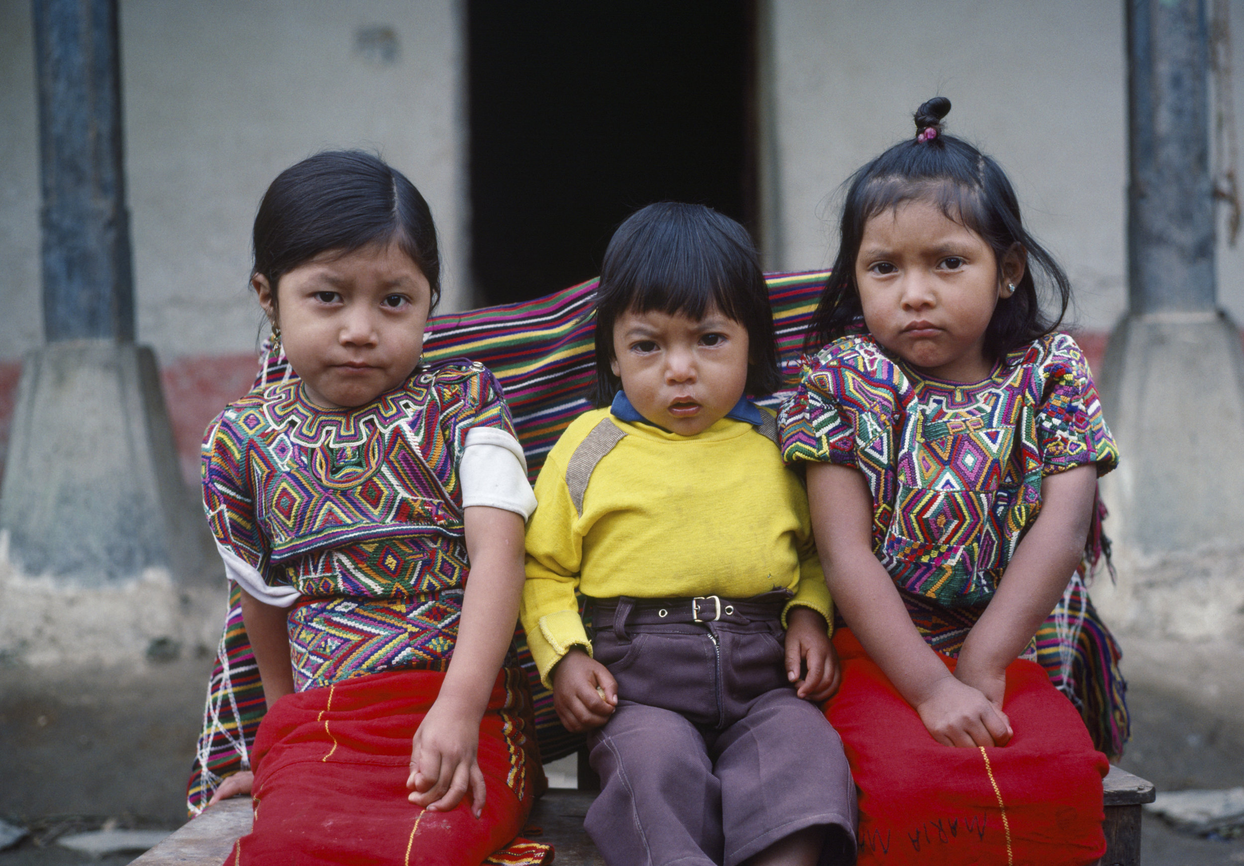Older sister Cedillo Marcos, 5 years, left, Pedro Cedillo Marcos, center, 2 years, Marcelina Cedillo Marcos, right, 4 years, sit for a photograph in the Pensíon Ardavin in Nebaj, Guatemala on January 1, 1984. Marcelina Cedillo Marcos grew up to be a schoolteacher and witnessed frequent armed violence of the civil war in the Ixil Maya region.