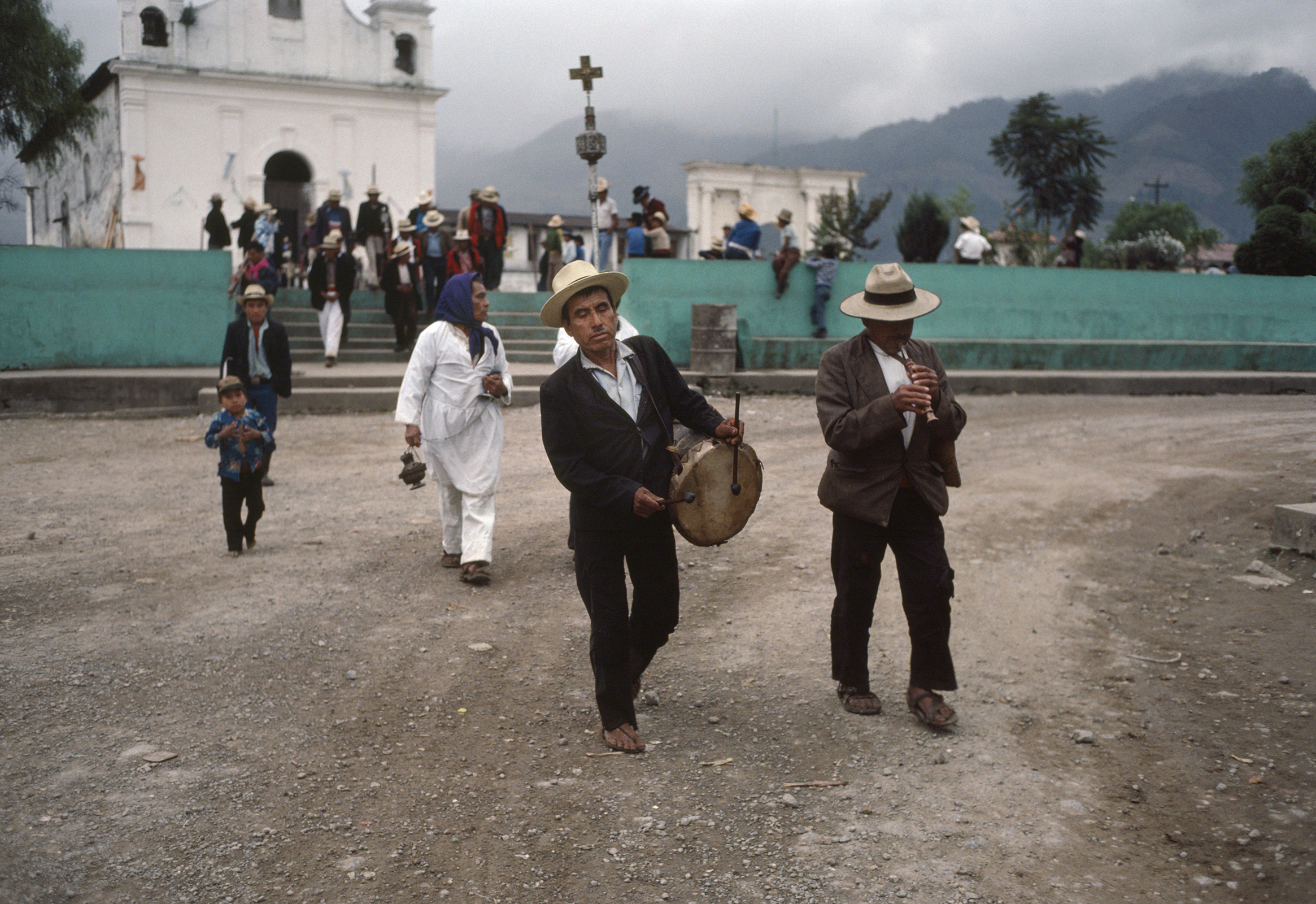 Ixil Maya men leave the central plaza following a Roman Catholic Church service in Nebaj, Guatemala on January 1, 1984. Religion played a fundamental role in the civil war for both the guerrilla insurgency, who sympathized with the socially progressive Catholic movement of liberation theology, and the Guatemalan state, who used Fundamental Protestantism, and specifically the evangelical movement, as a means to stifle opposition to the military dictatorship and subvert the expansion of liberties and individual responsibility promoted through liberation theology.