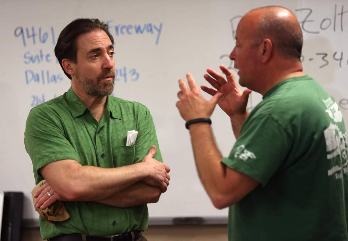 Clinic leader and immigration lawyer Paul Zoltan (left) listens to questions from lawyer Brett Foster while helping a minor with immigration and asylum documents. (Ricky Moon/Dallas Morning News Special Contributor)