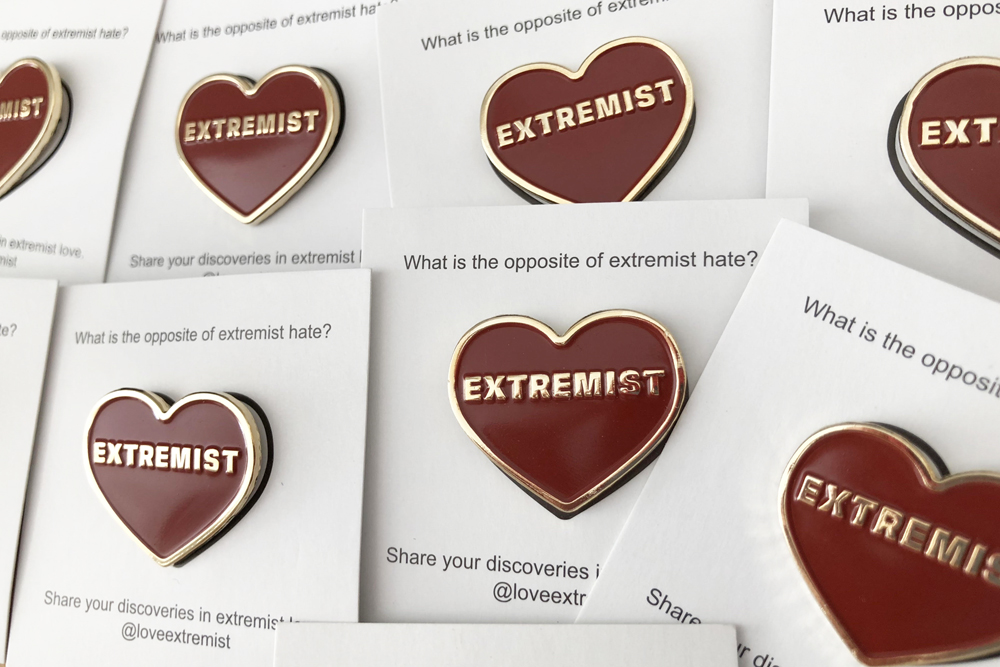 Each pin is mounted on a paper backing with details about Love Extremist