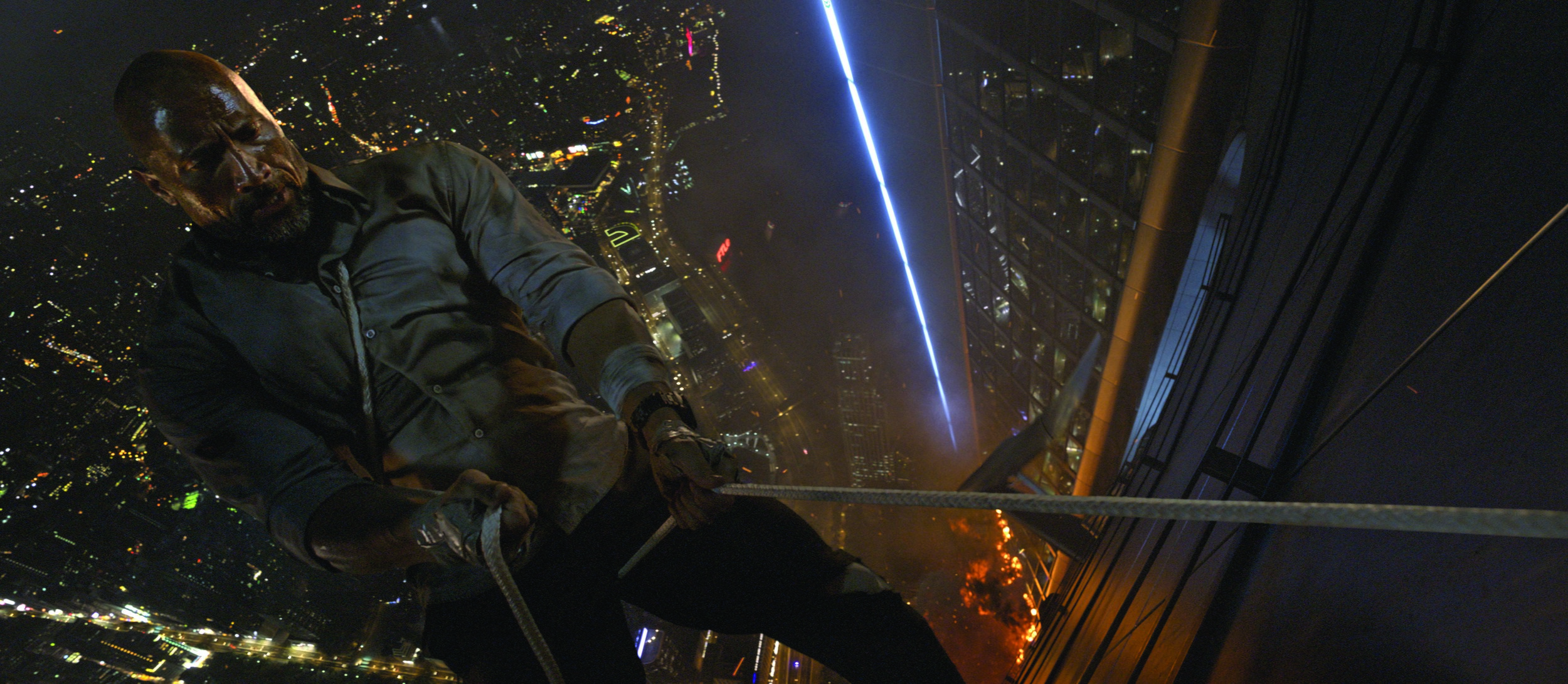 "Dwayne Johnson plays Will Sawyer, a security consultant who must risk his life to save his family from a burning Hong Kong high rise in ""Skyscraper."" (Photo courtesy Legendary Pictures / Universal Pictures)"
