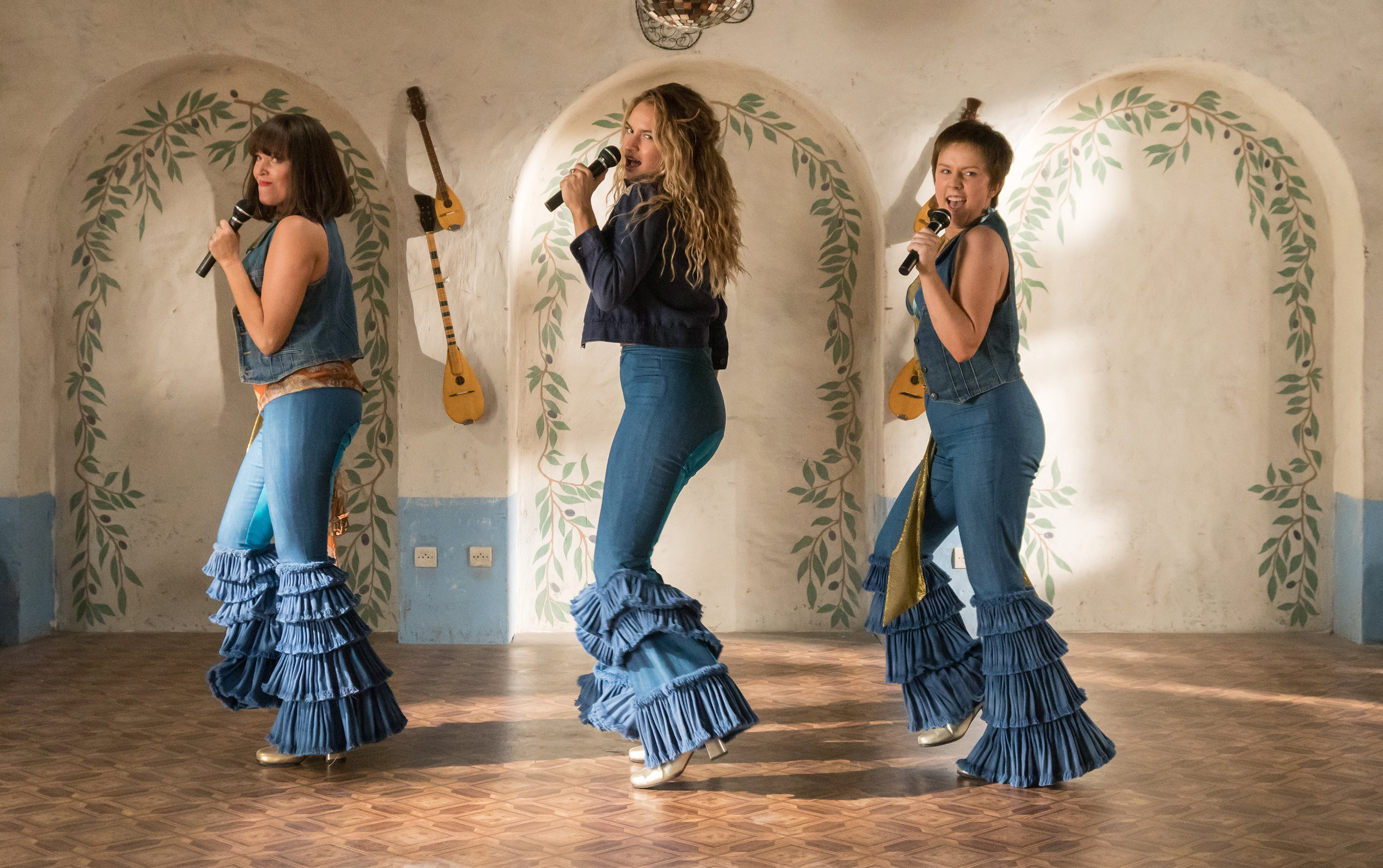 """Donna (Lily James, center) and the Dynamos — Tanya (Jessica Keenan Wynn, left) and Rosie (Alexa Davies, right) — in their younger incarnation, in the musical """"Mamma Mia! Here We Go Again."""" (Photo by Jonathan Prime / Universal Studios)"""
