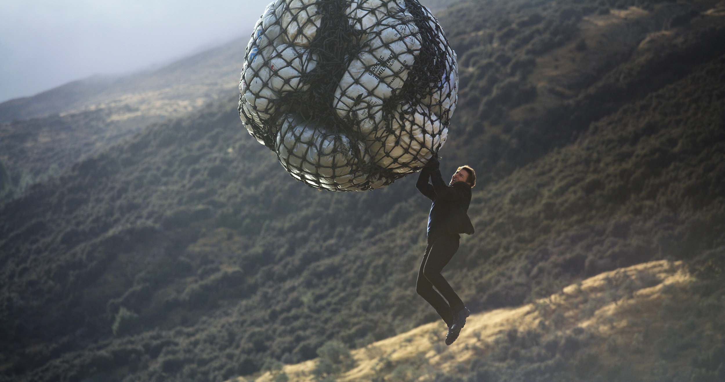 """Tom Cruise returns as superspy Ethan Hunt, riding a helicopter's payload, in """"Mission: Impossible - Fallout,"""" the sixth movie in the long-running franchise. (Photo courtesy Paramount Pictures)"""