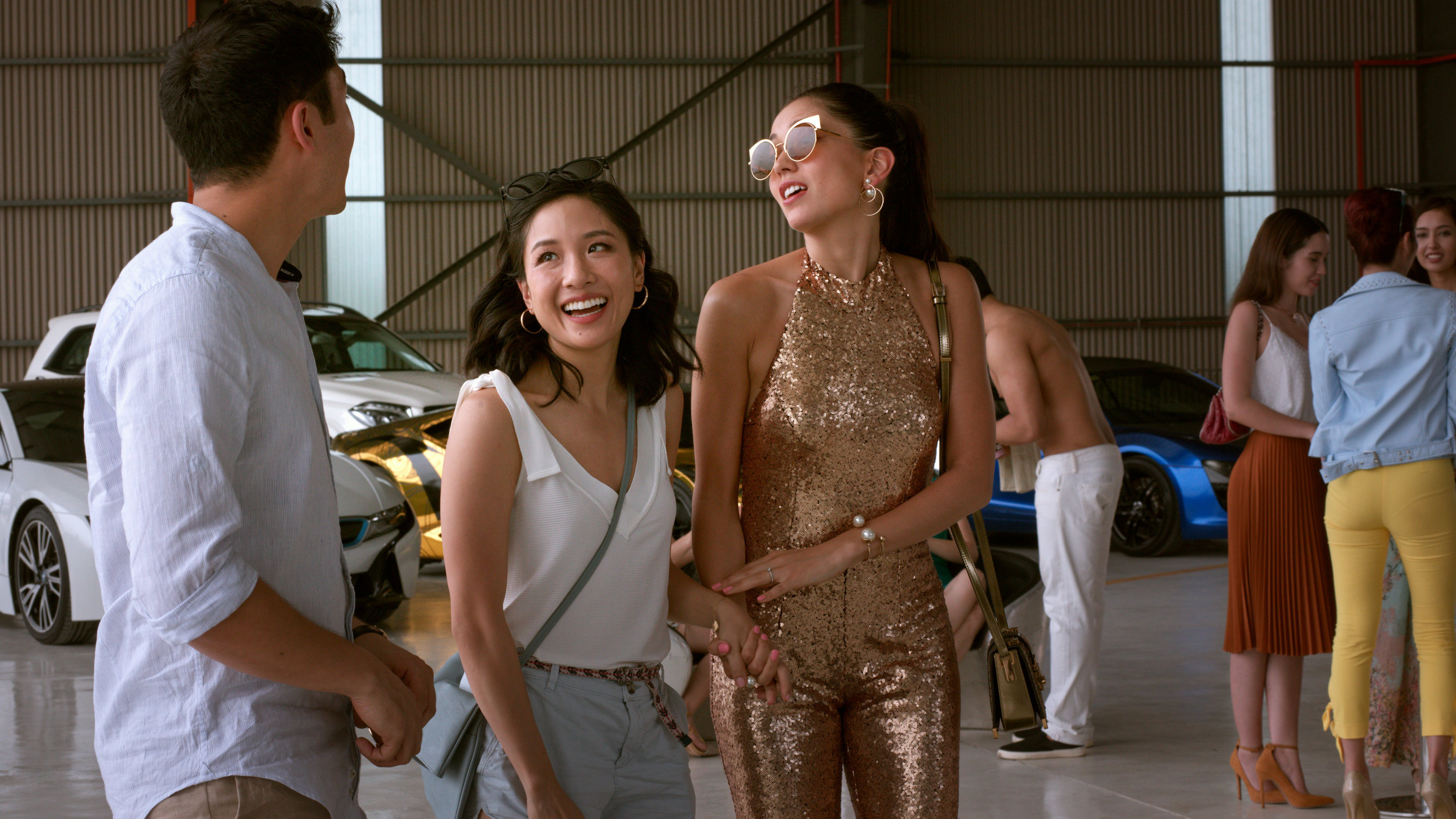 """Rachel Chu (Constance Wu, center) gets a crash course in the super-rich when her boyfriend Nick (Henry Golding, left) brings her to Singapore for a friend's wedding — and the bachelorette party for the bride, Araminta (Sonoya Mizuno, right) — in the comedy """"Crazy Rich Asians."""" (Photo by Sanja Bucko, courtesy of Warner Bros. Pictures)"""