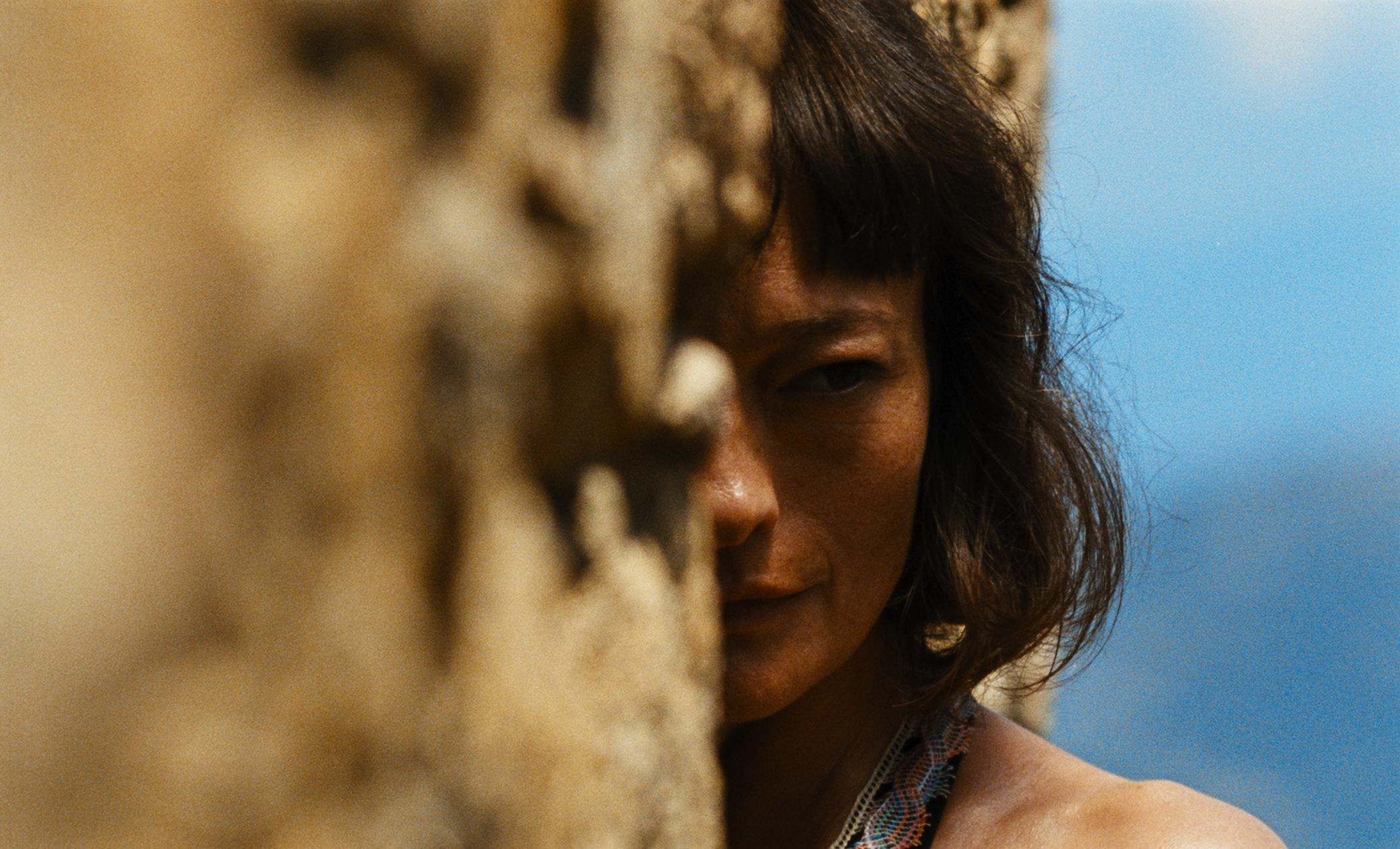 """Luce (Elina Löwensohn), a jaded artist, sizes up the carnage going on around her villa retreat, in the French-Belgian crime drama """"Let the Corpses Tan."""" (Photo courtesy Kino Lorber Films)"""