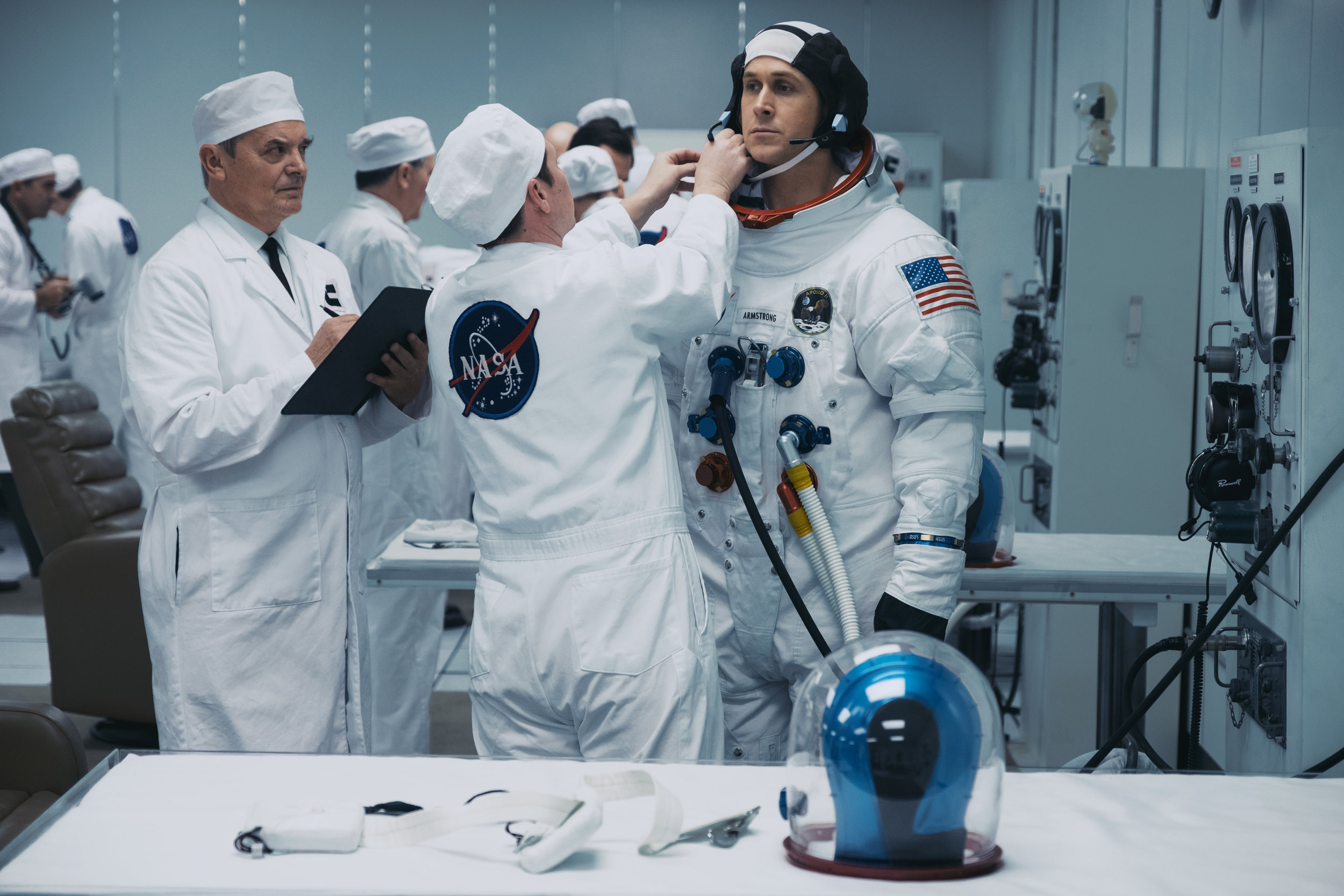 """Technicians put astronaut Neil Armstrong (Ryan Gosling) into his spacesuit in preparation for the Apollo 11 mission to the moon, in director Damien Chazelle's """"First Man."""" (Photo by Daniel McFadden, courtesy of Universal Pictures / DreamWorks Pictures)"""