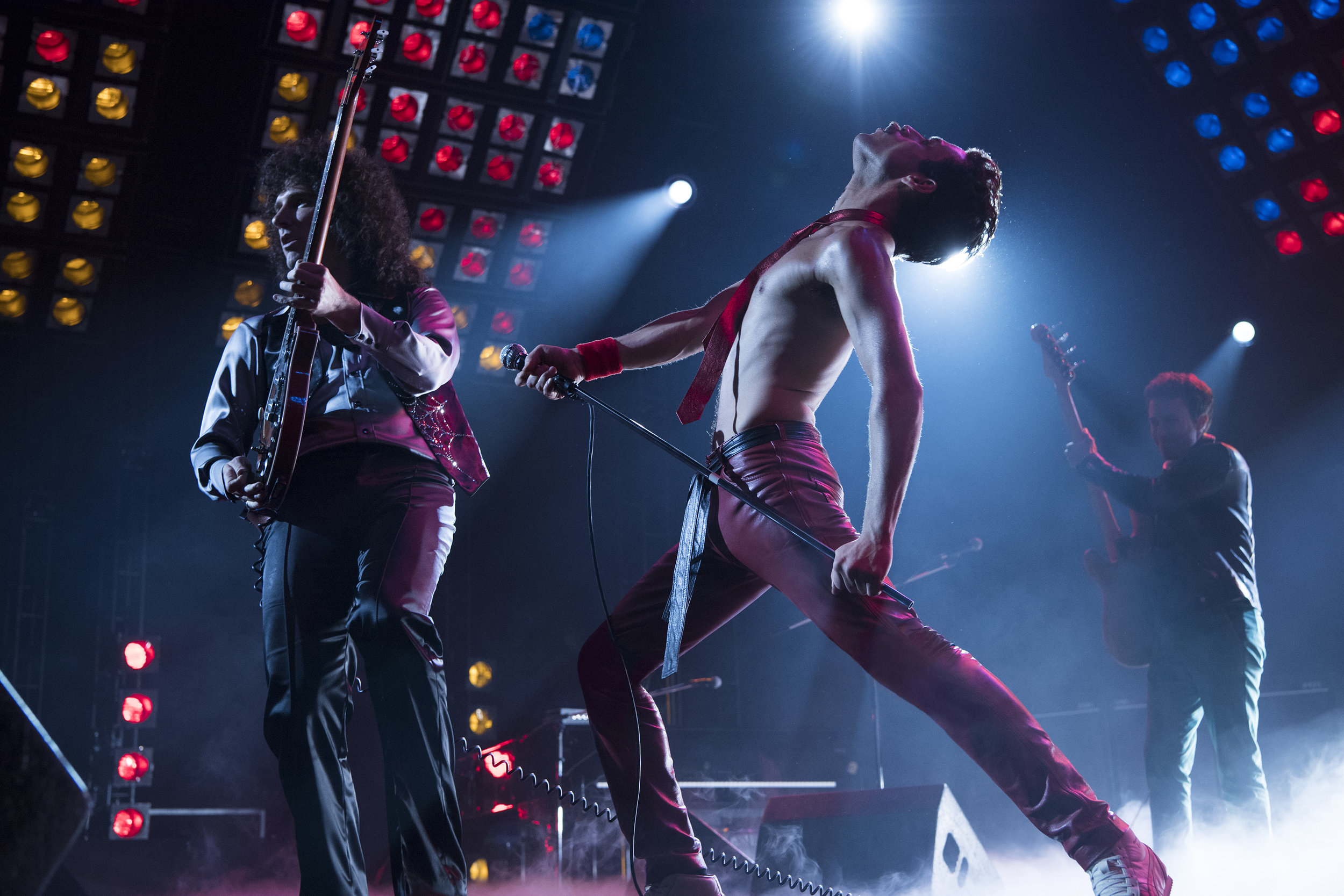 """The members of Queen — from left, Brian May (Gwilym Lee), Freddie Mercury (Rami Malek) and John Deacon (Joe Mazzello) — perform in a scene from the biographical drama """"Bohemian Rhapsody."""" (Photo by Alex Bailey, courtesy 20th Century Fox)"""