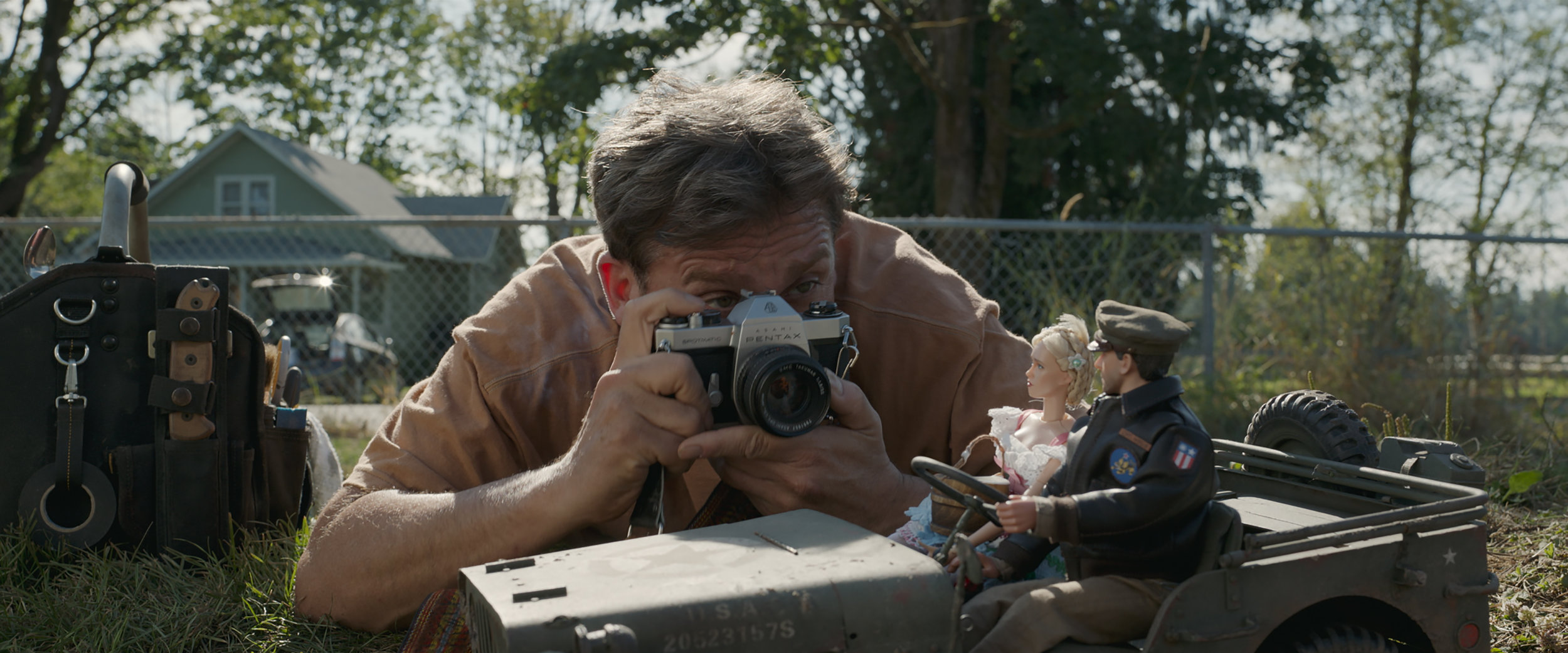"Mark Hogancamp (Steve Carell) photographs the figures in his installation, a scale model of a Belgian town in World War II, in the drama ""Welcome to Marwen."" (Photo courtesy Universal Pictures/Dreamworks Pictures)"