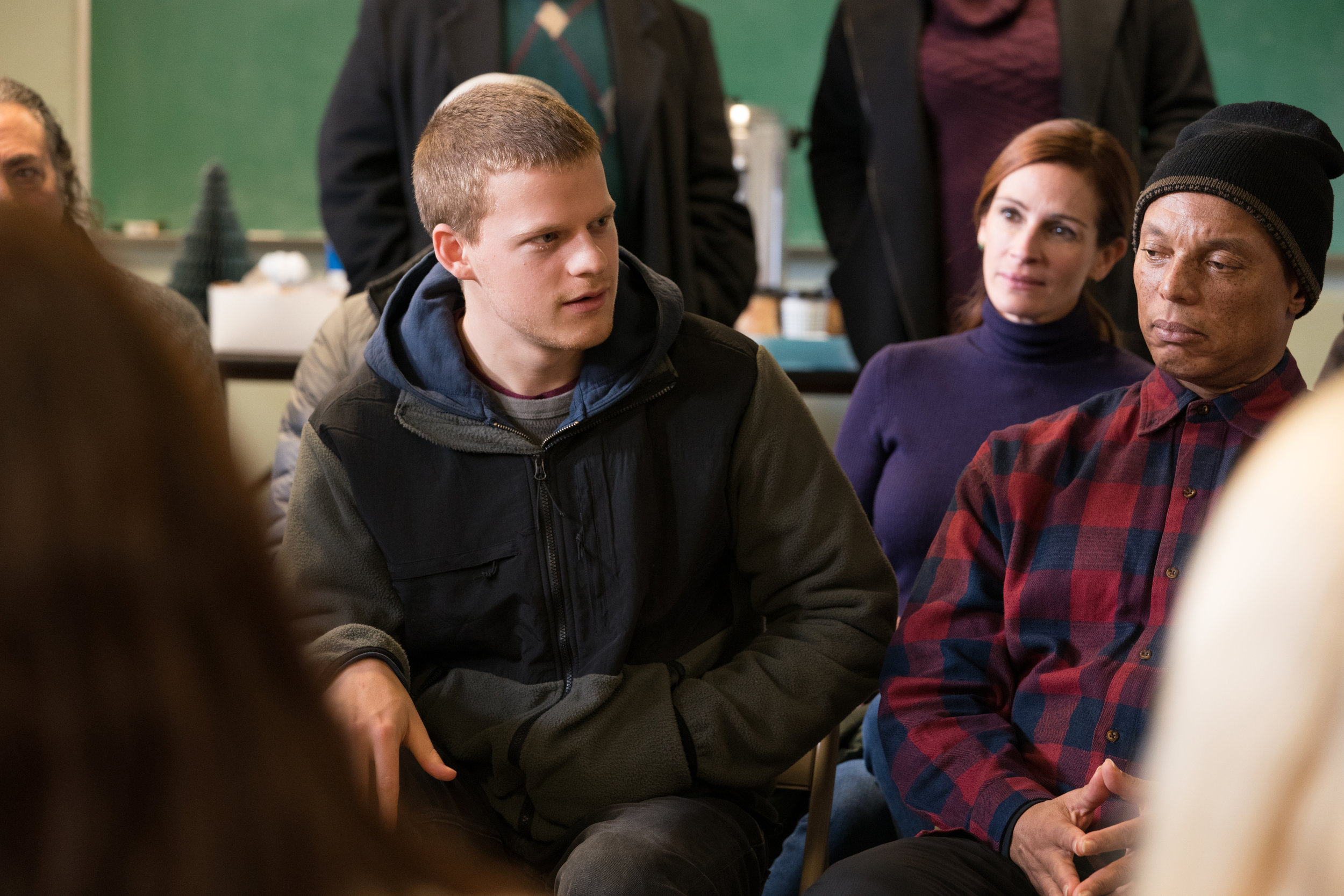 """Ben (Lucas Hedges, center) speaks during a Narcotics Anonymous meeting, accompanied by his mom, Holly (Julia Roberts, background), in the drama """"Ben Is Back."""" (Photo by Mark Schafer, courtesy LD Entertainment and Roadside Attractions)"""