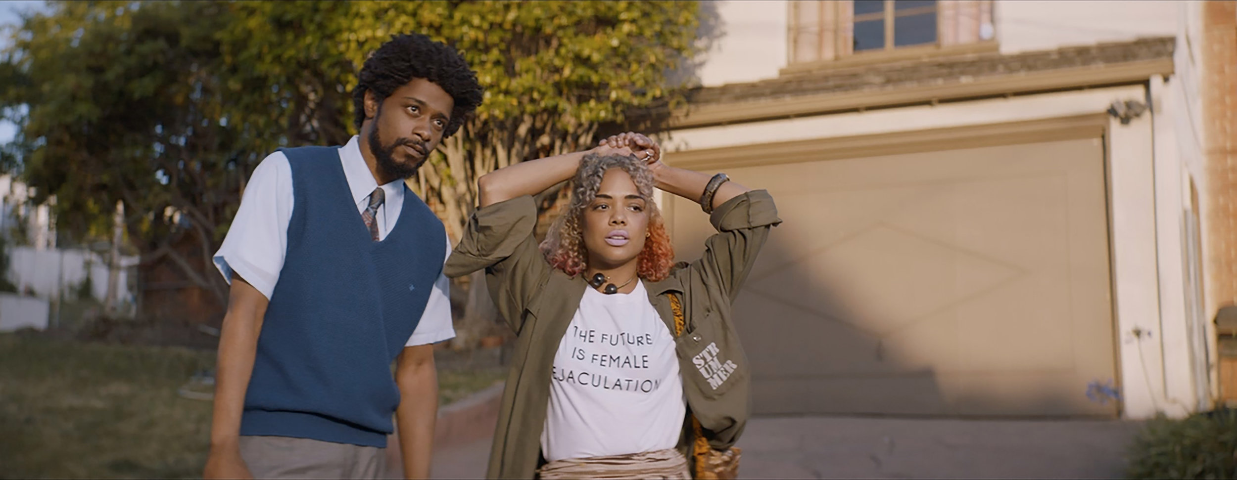 "Cassius Green (Lakeith Stanfield, left) and his artist girlfriend, Detroit (Tessa Thompson), navigate poverty, sudden wealth and racism in Boots Riley's satire ""Sorry to Bother You."" (Photo courtesy Annapurna Pictures)"