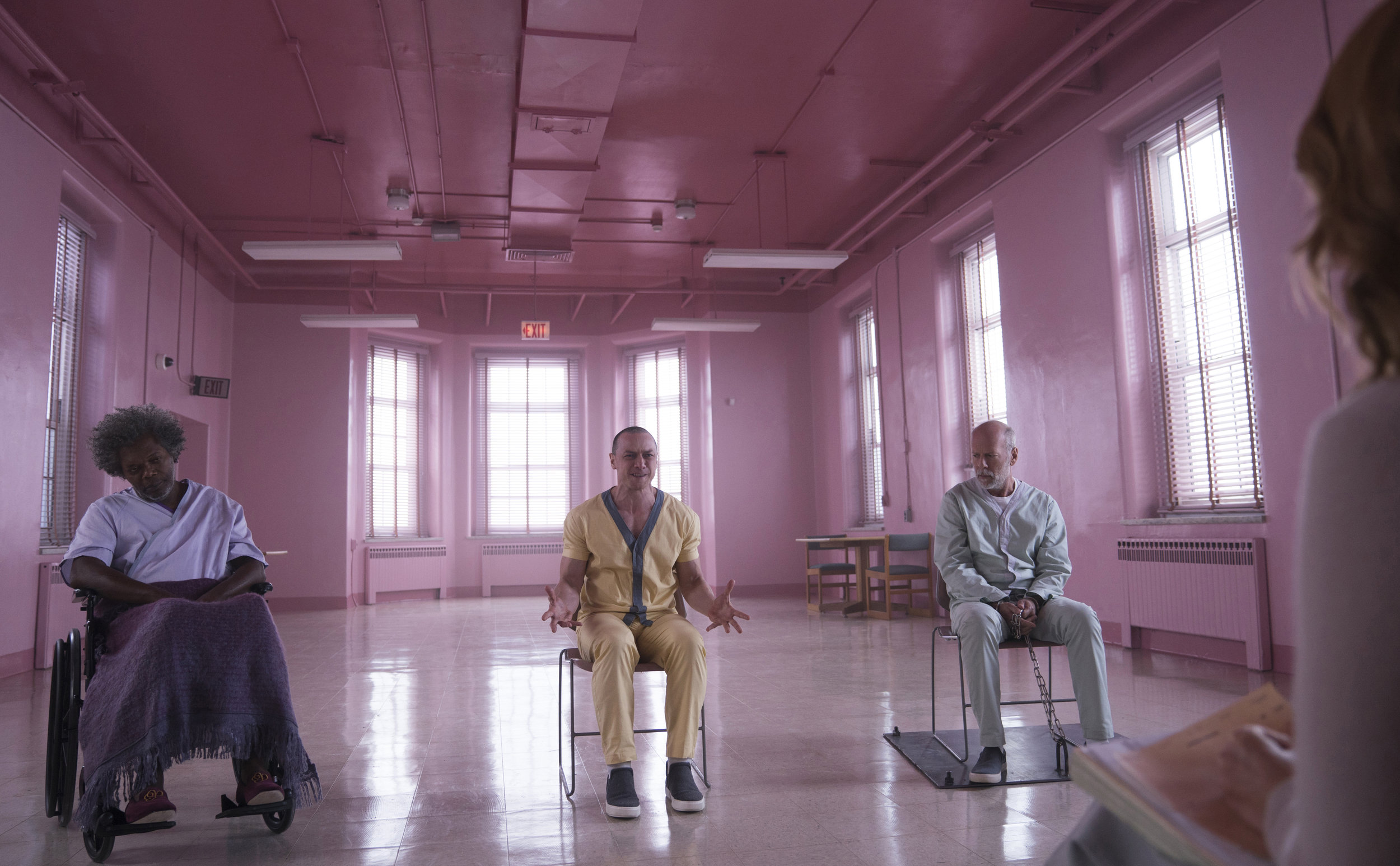 """Dr. Ellie Sample (Sarah Paulson, right) interviews three mental patients — from left, Elijah Price/Mr. Glass (Samuel L. Jackson), Kevin Crump aka The Horde (James McAvoy), and David Dunn (Bruce Willis — in M. Night Shyamalan's thriller """"Glass."""" (Photo by Jessica Kourkounis, courtesy Universal Pictures)"""