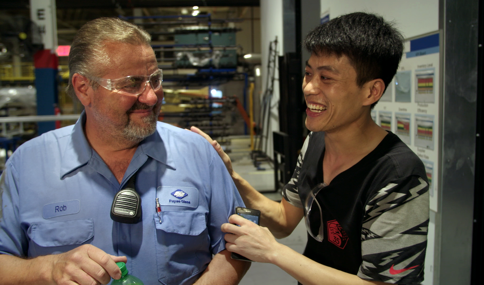 """Rob Haerr, left, and Wong He, are unexpected co-workers at an Ohio auto-glass plant begun by a Chinese billionaire, in """"American Factory,"""" by Steve Bognar and Julia Reichert, an official selection in the U.S. Documentary Competition of the 2019 Sundance Film Festival. (Photo by Ian Cook, courtesy Sundance Institute)"""