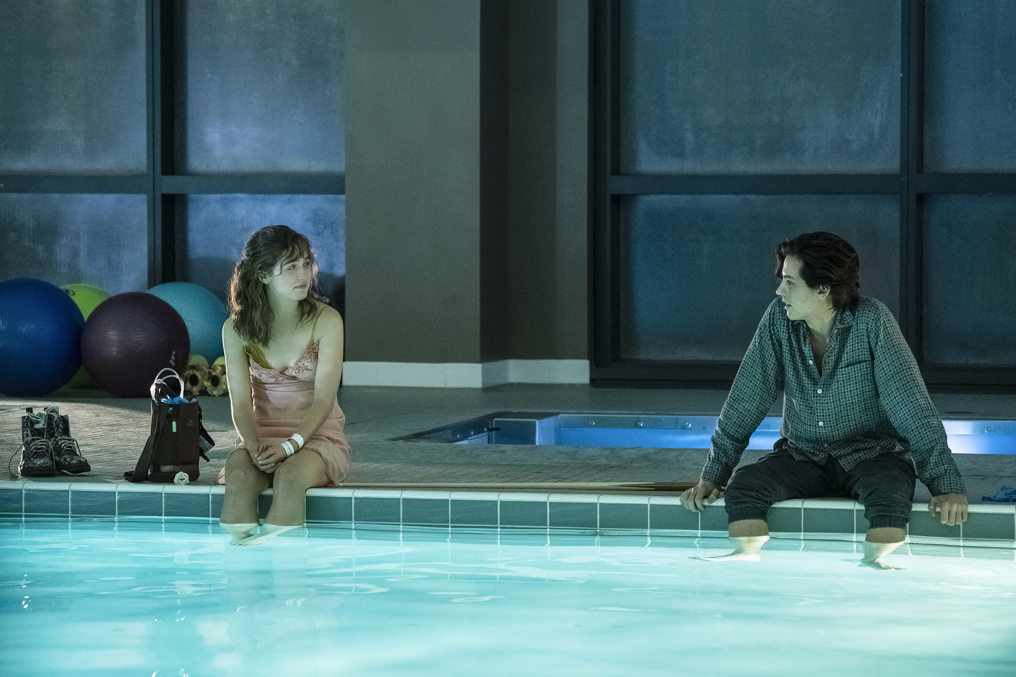 """Stella (Haley Lu Richardson, left) and Will (Cole Sprouse), teens in love and battling cystic fibrosis, share a date, at a distance, in the romantic drama """"Five Feet Apart."""" (Photo by Alfonso Bresciani, courtesy CBS Films / Lionsgate)"""