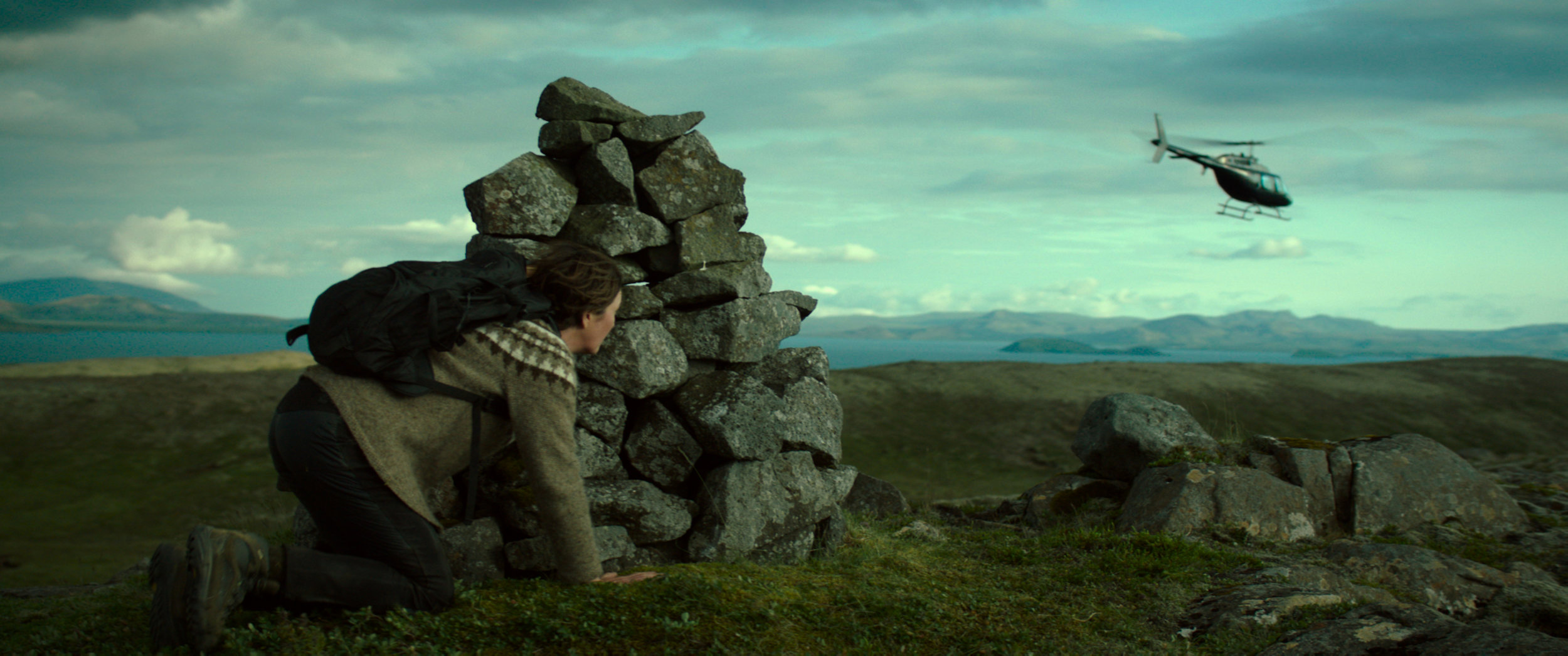 "Halla (Halldóra Geirharðsdóttir) hides from police helicopters after committing some ecological espionage in the Icelandic drama ""Woman at War."" (Photo courtesy Magnolia Pictures.)"