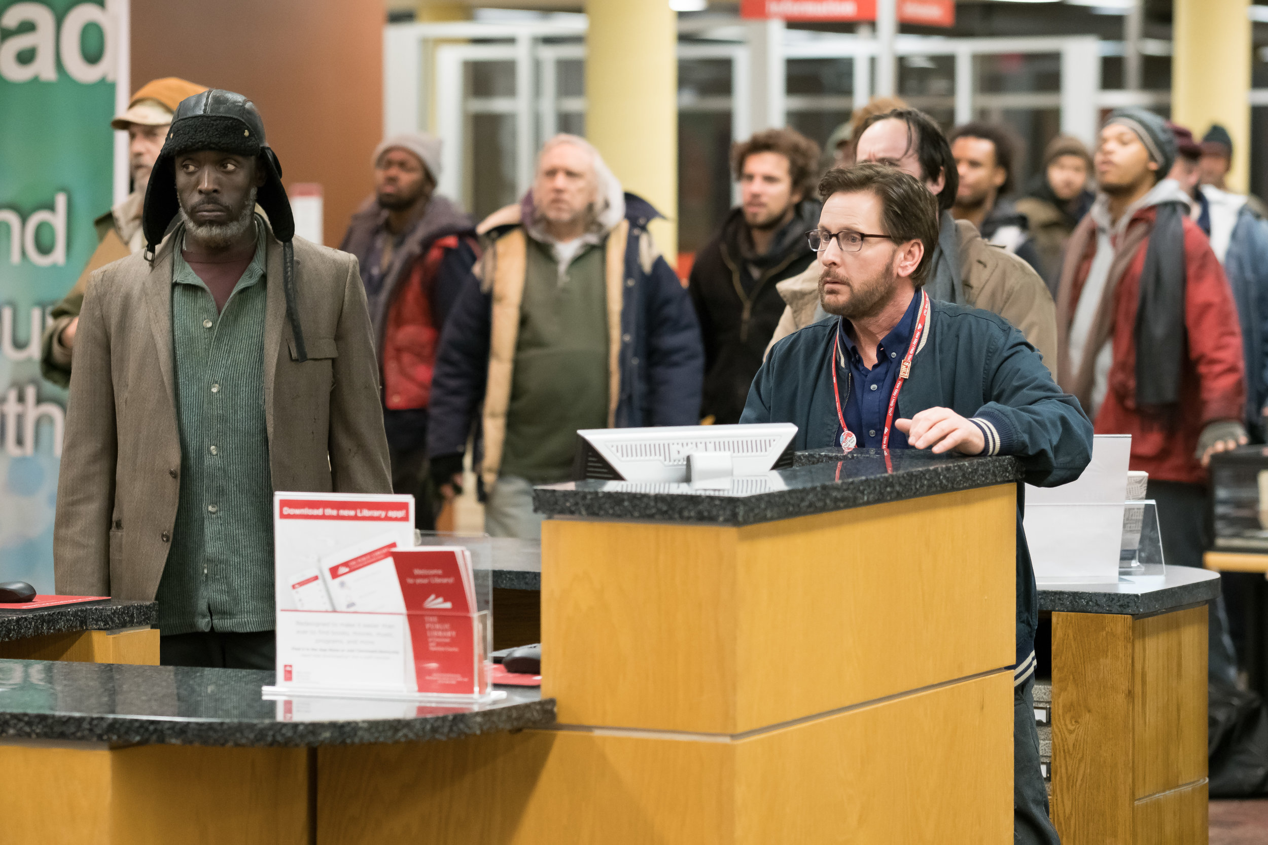 """Librarian Stuart Goodson (Emilio Estevez, center) becomes the spokesman for a group of homeless people, including Jackson (Michael K. Williams, at left), who have staged a sit-in at The Public Library of Cincinnati, in the comedy-drama """"The Public,"""" written and directed by Estevez. (Photo courtesy Greenwich Entertainment)"""