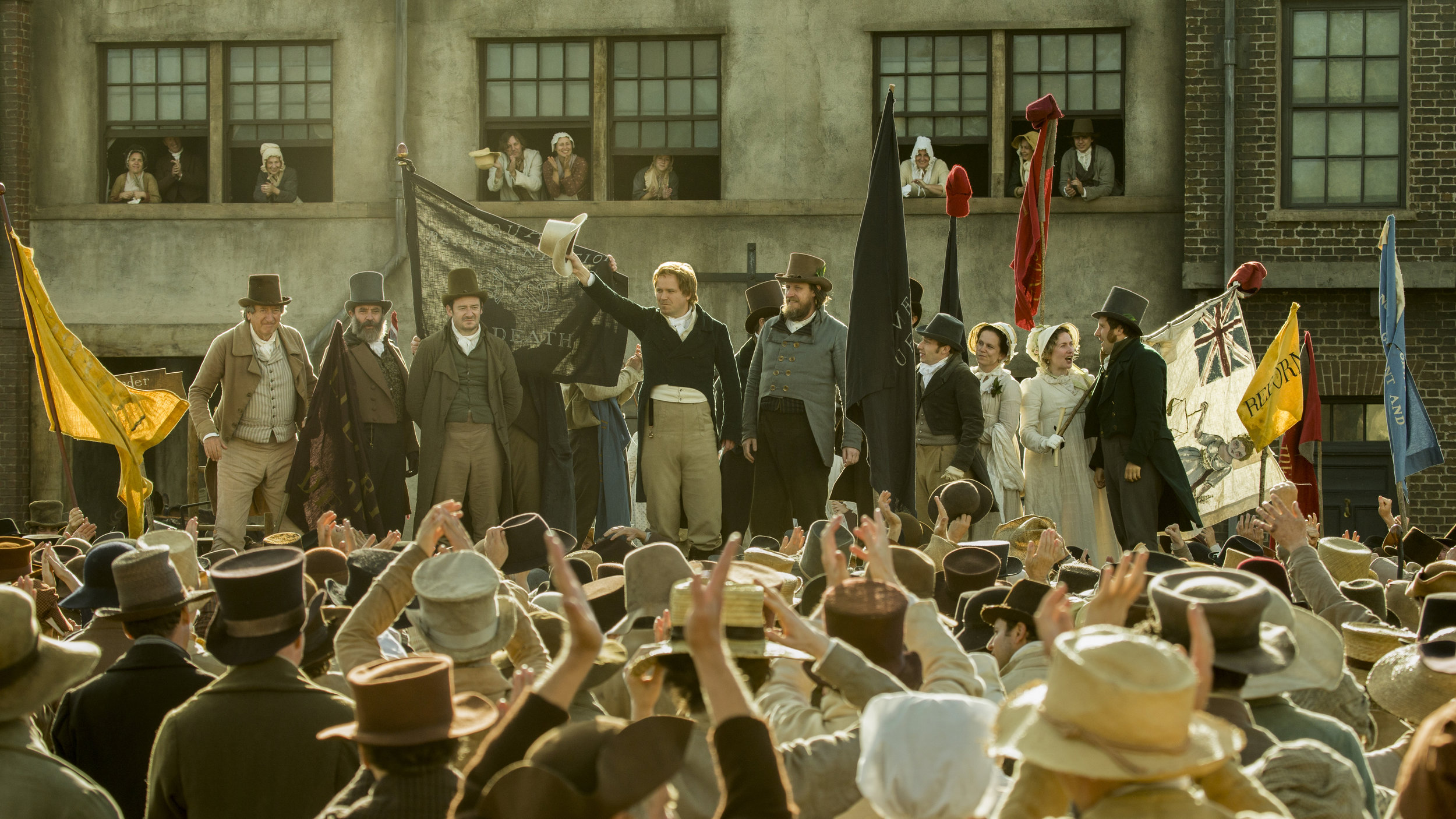 """Reformer Henry Hunt (Rory Kinnear, center, with white hat in hand) waves to the crowds in Manchester's St. Peter's Field, in a scene from Mike Leigh's historical drama """"Peterloo."""" (Photo by Simon Mein, courtesy  Amazon Studios.)"""