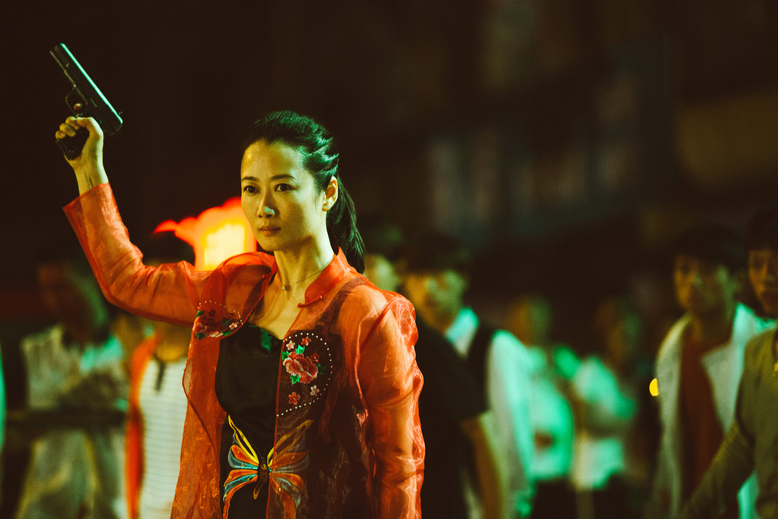 "Qiao (Zhao Tao) raises a gun into the air to warn off the thugs beating up her gangster boyfriend in Jia Zhang-ke's modern Chinese drama ""Ash Is Purest White."" (Photo courtesy of Cohen Media Group.)"